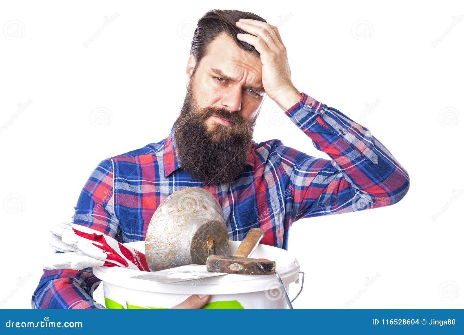 拿着使用的石工工具的哀伤的有胡子的人