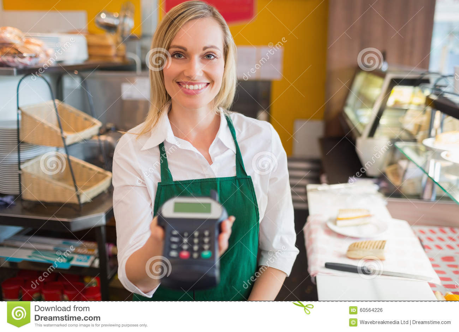 拿着信用卡读者的愉快的女性店主