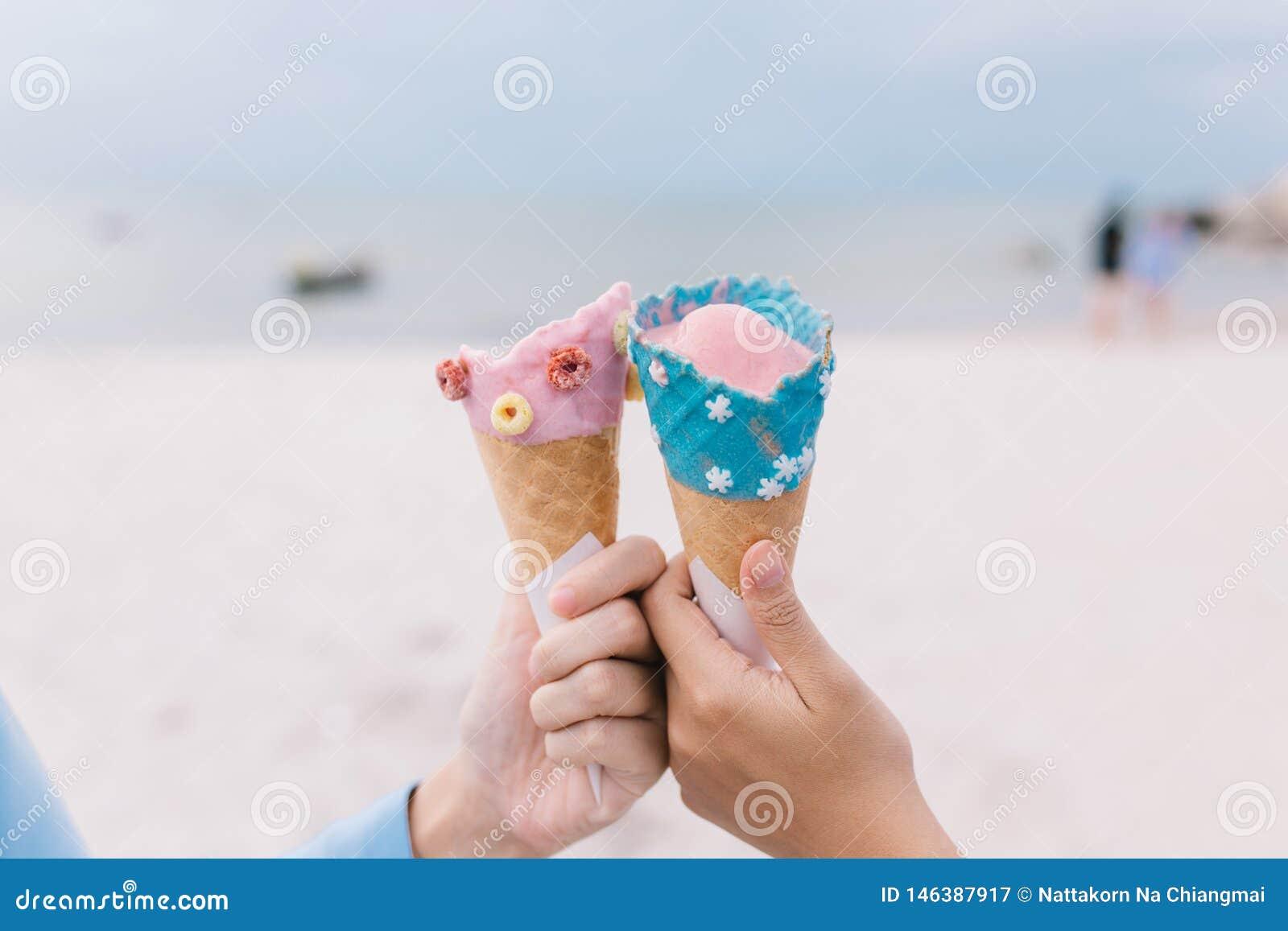 拿着冰淇淋锥体的两名手青少年妇女在夏天在海滩和海