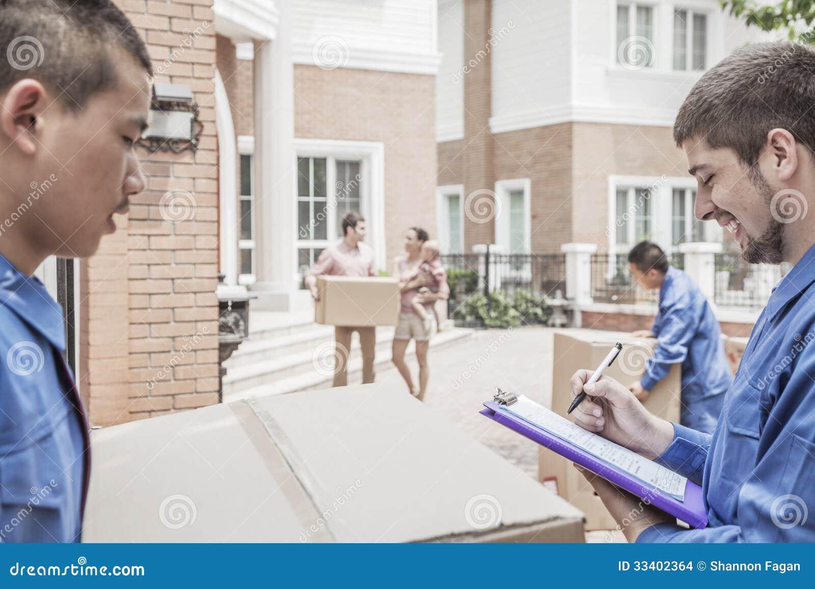 拿着剪贴板和发货票,家庭的搬家工人在背景中