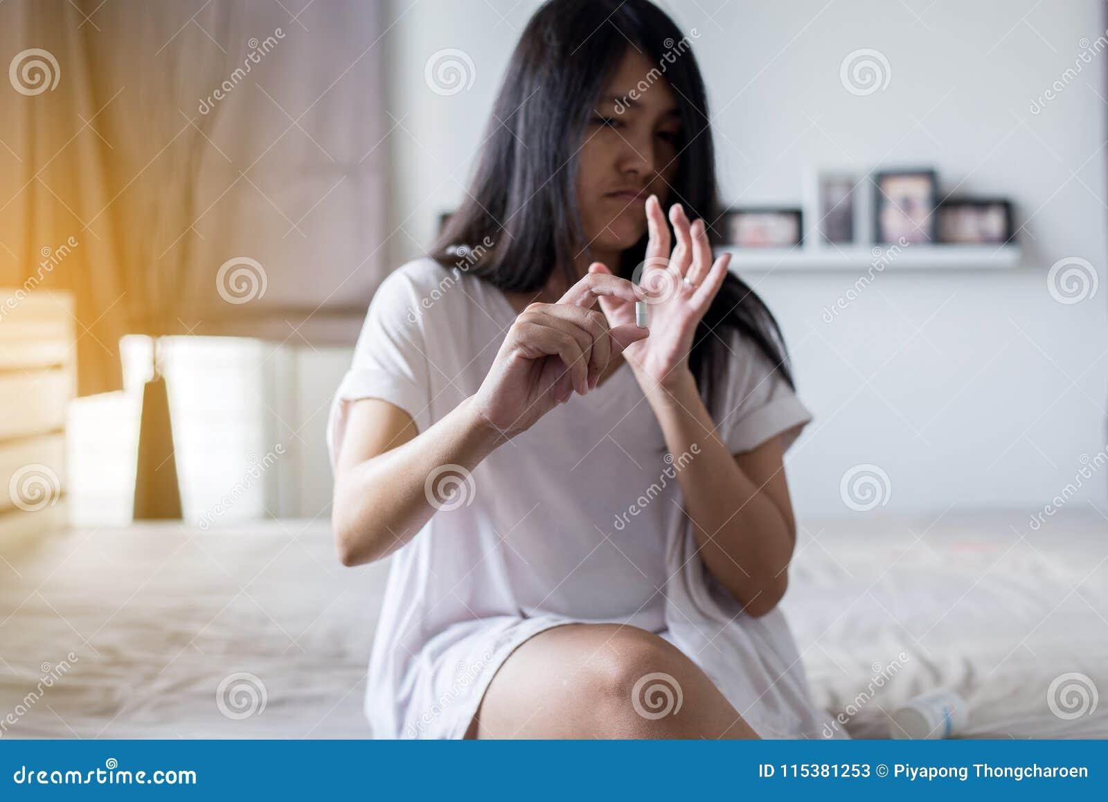 拿着医学,有药片的妇女手的女性手在溢出药片,但是不采取医学,情感面孔表示
