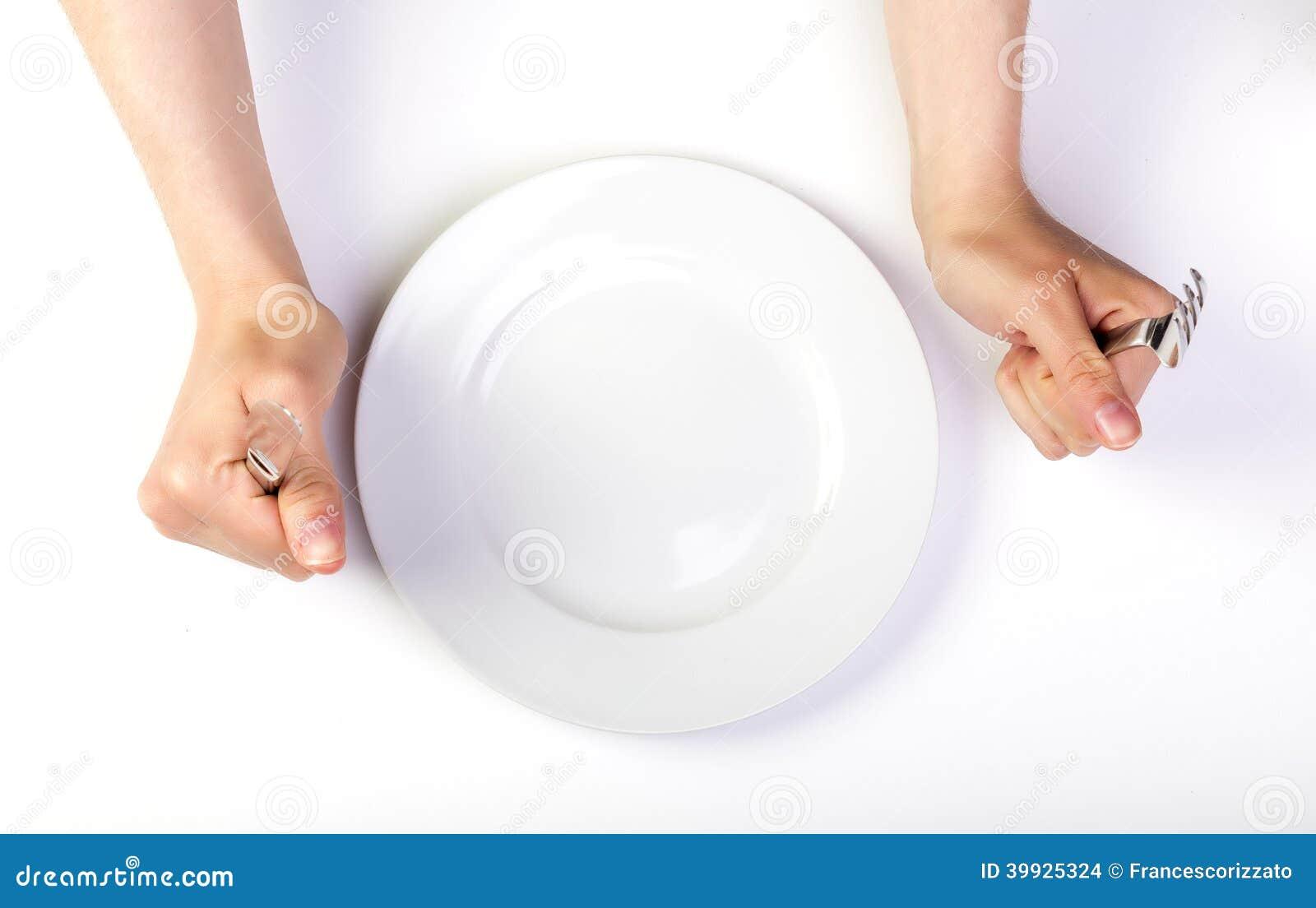 拿着叉子和刀子的女性手在一块空的板材旁边