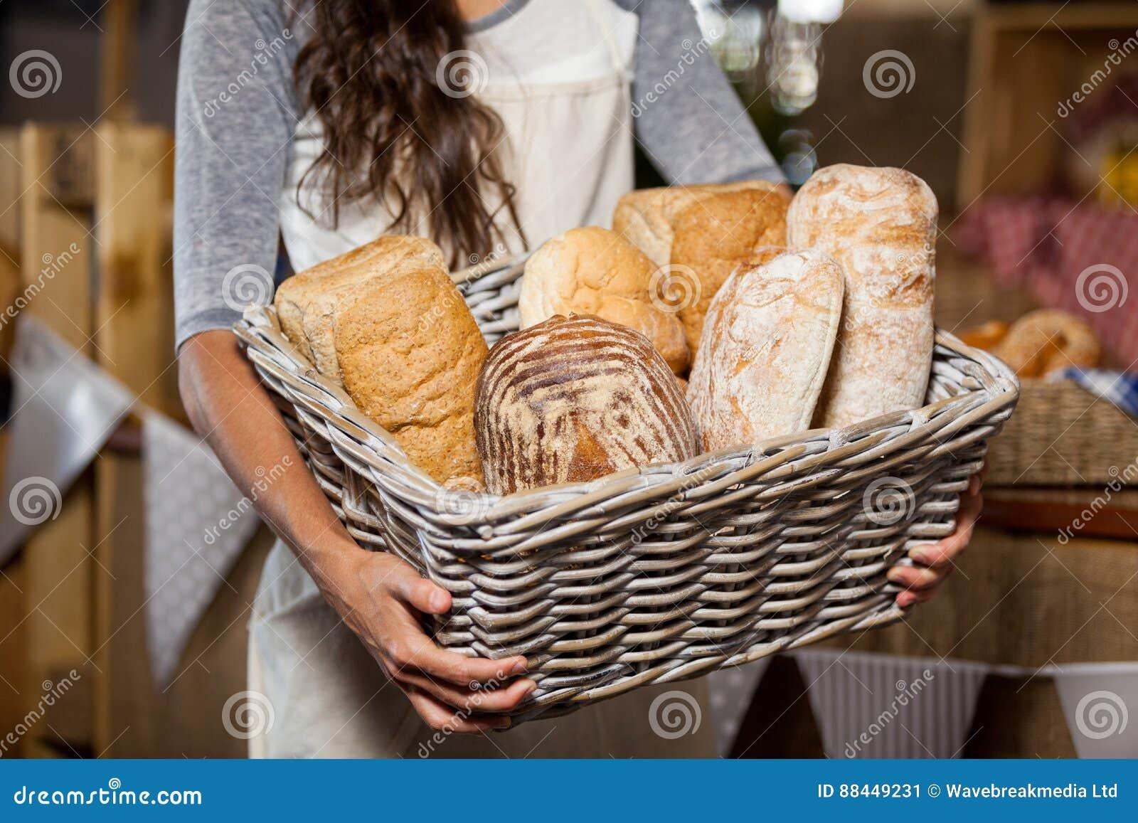 拿着各种各样的面包的柳条筐女职工在柜台在面包店商店
