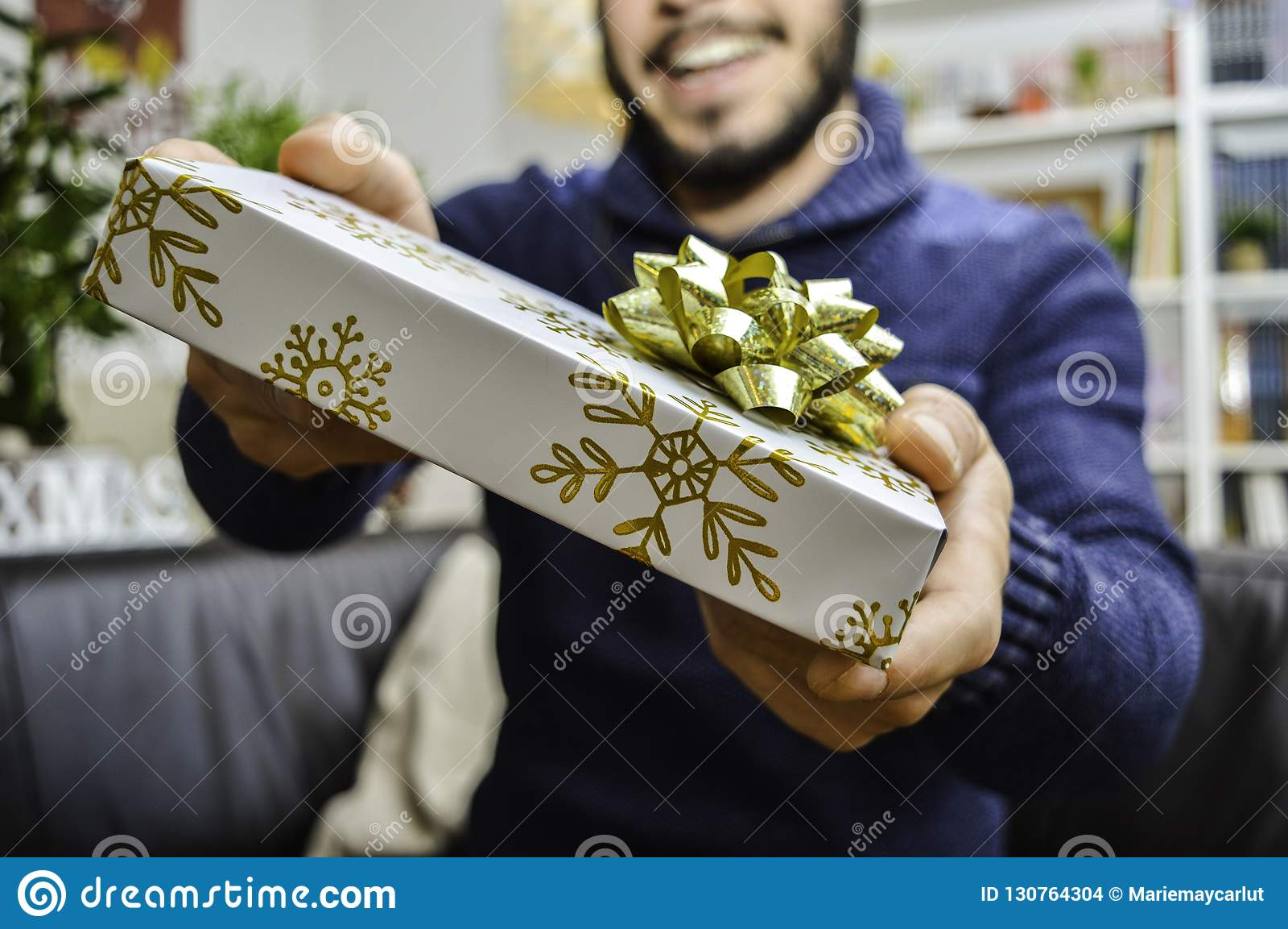 拿着和给礼物的愉快的年轻帅哥某人