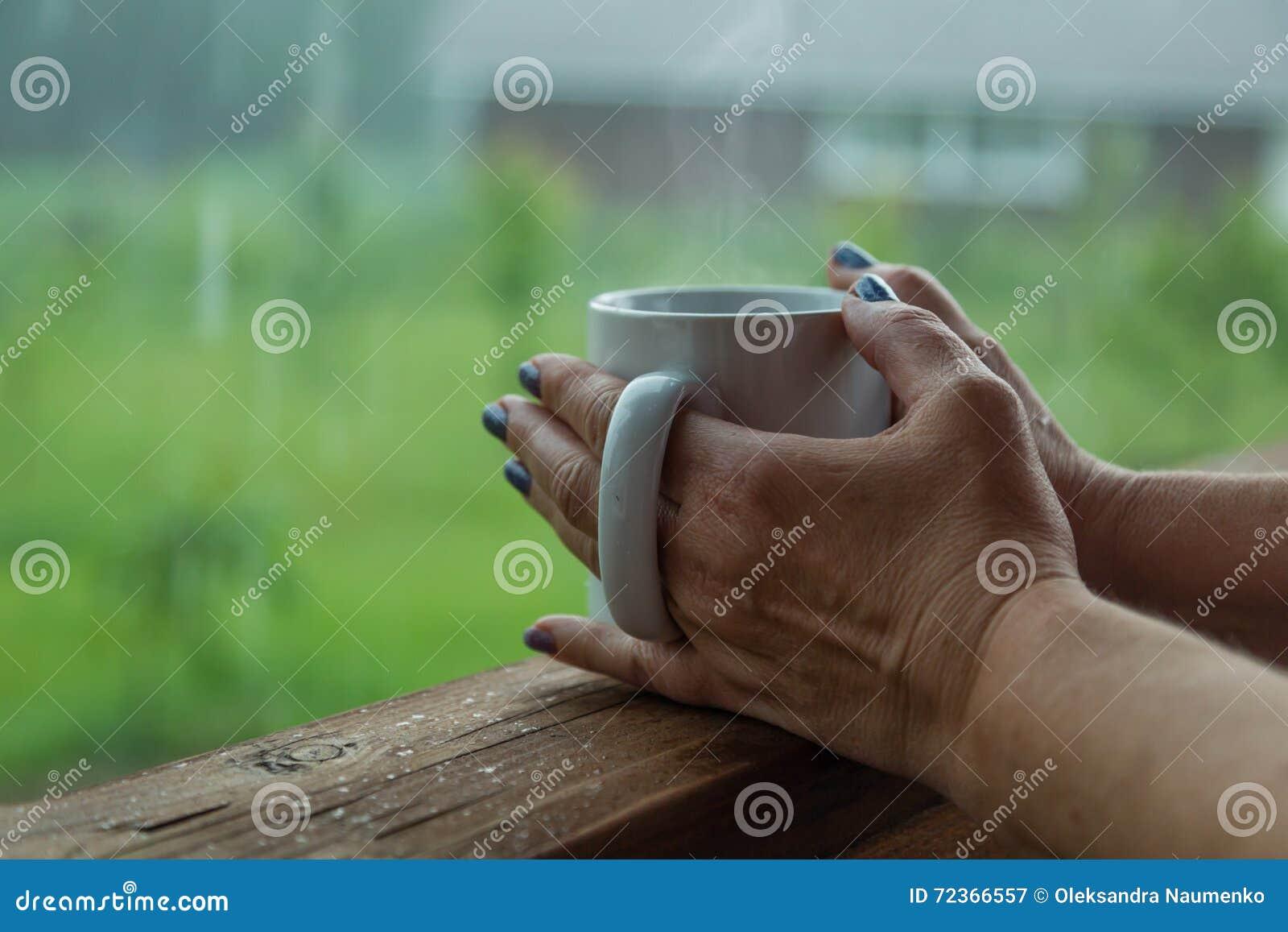 拿着咖啡的女性手在雨天
