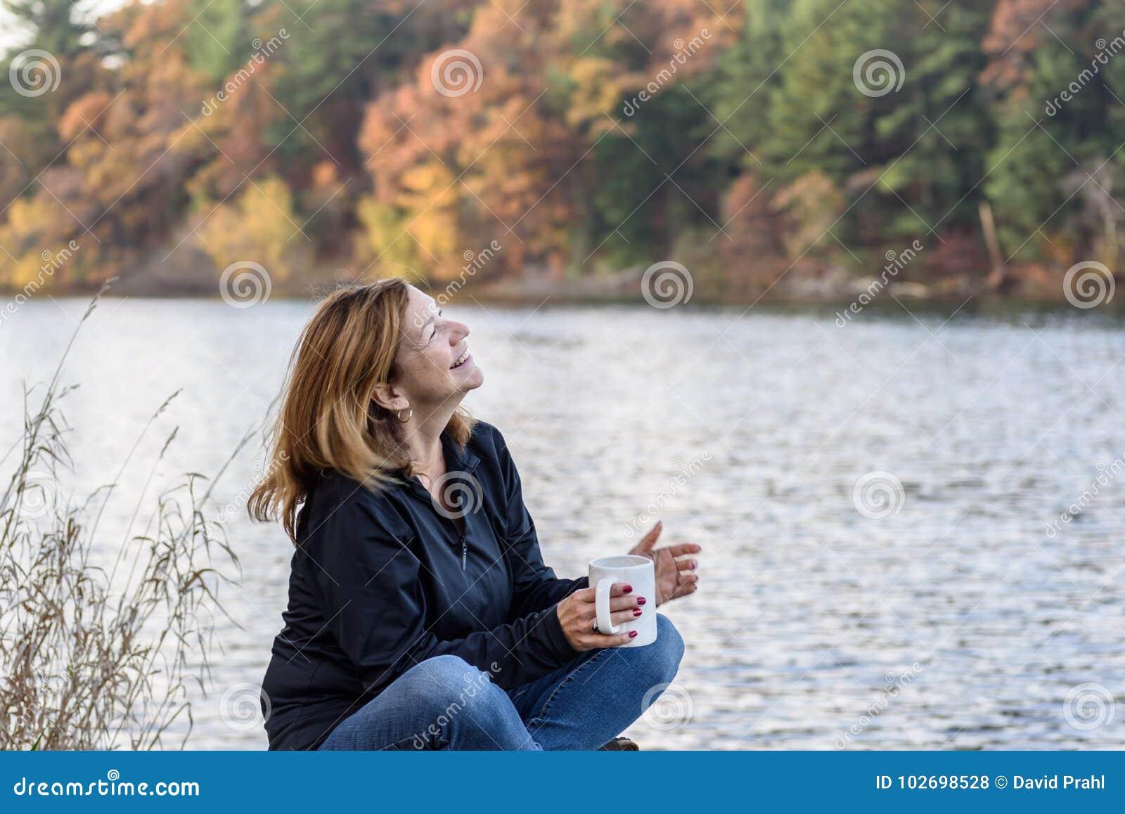 拿着咖啡的妇女笑沿有colorf的湖边平地