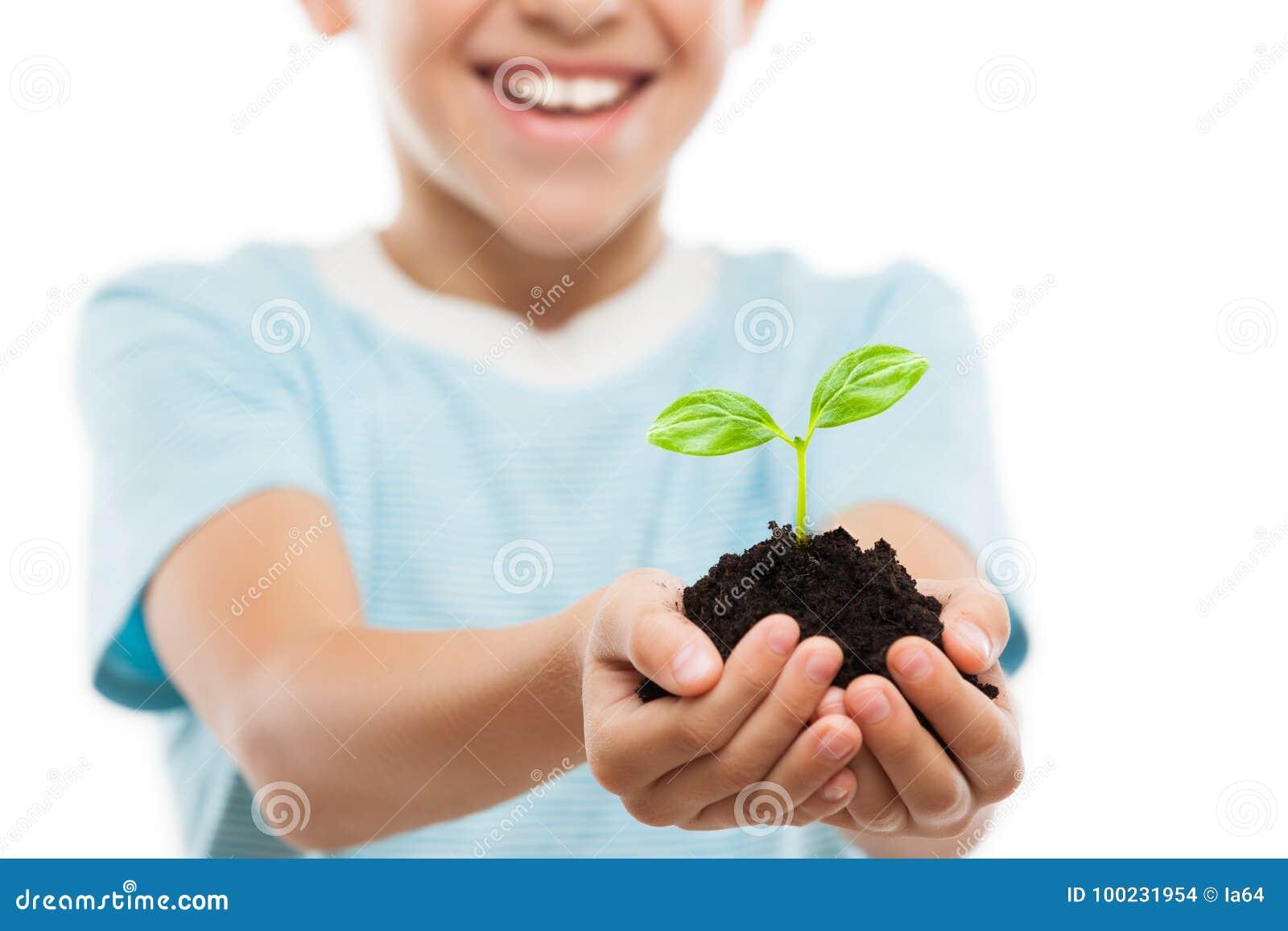 拿着土壤生长绿色新芽叶子的英俊的微笑的儿童男孩
