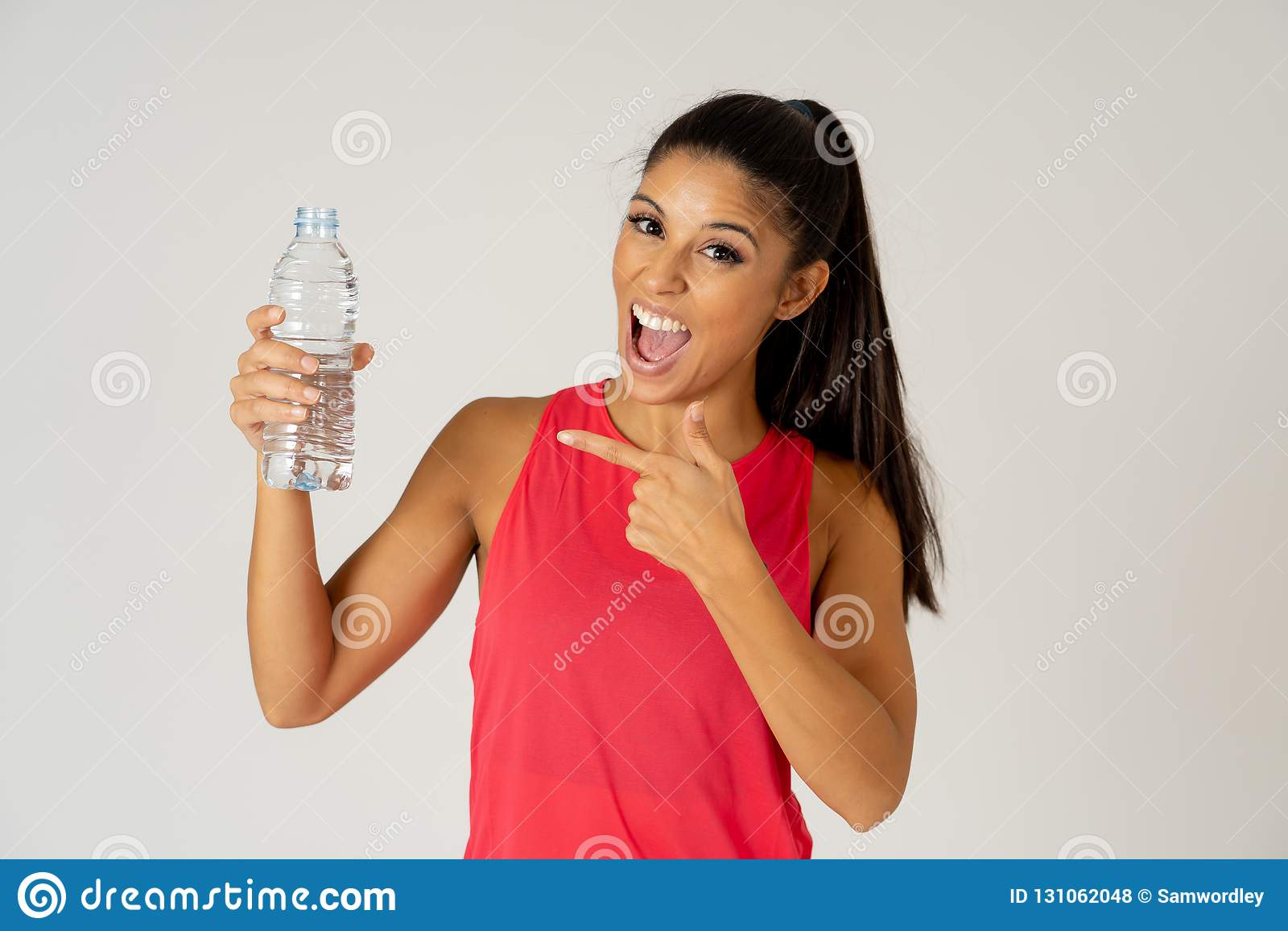 拿着在健康生活方式概念的健康可爱的体育妇女水瓶