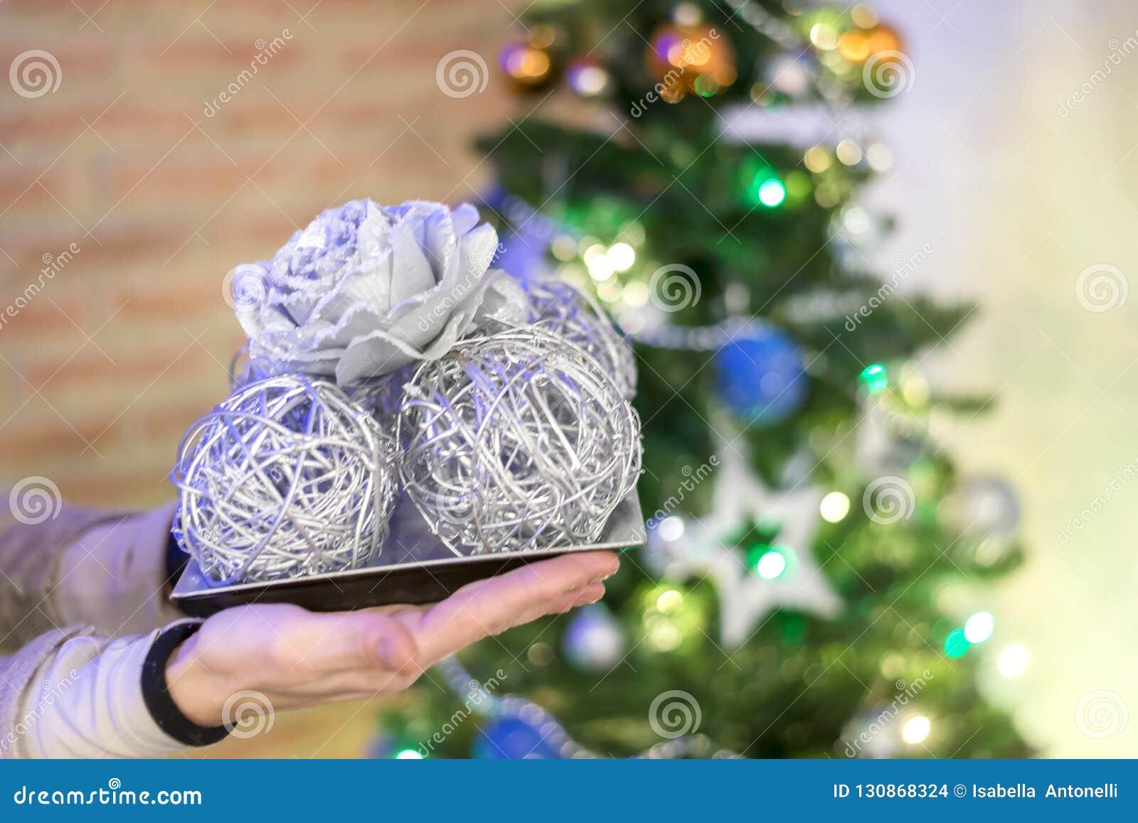 拿着在光背景的妇女圣诞节球