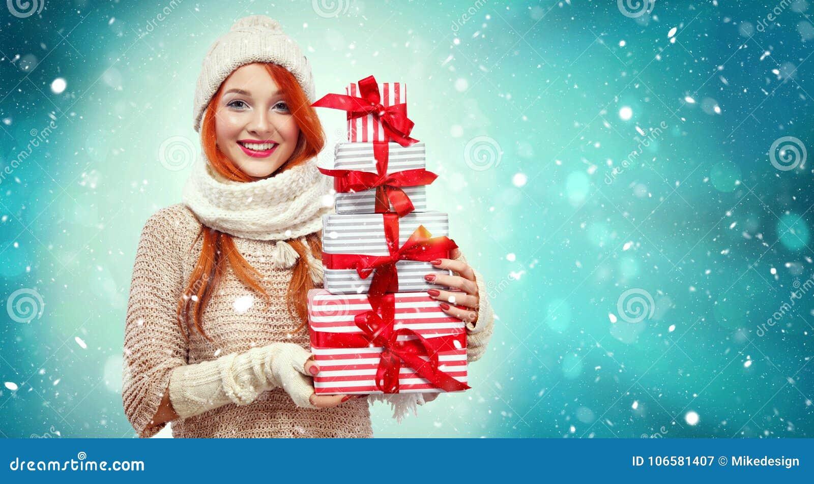 拿着在冬天背景的购物妇女礼物盒与雪在黑星期五,圣诞节和新年假日 销售额