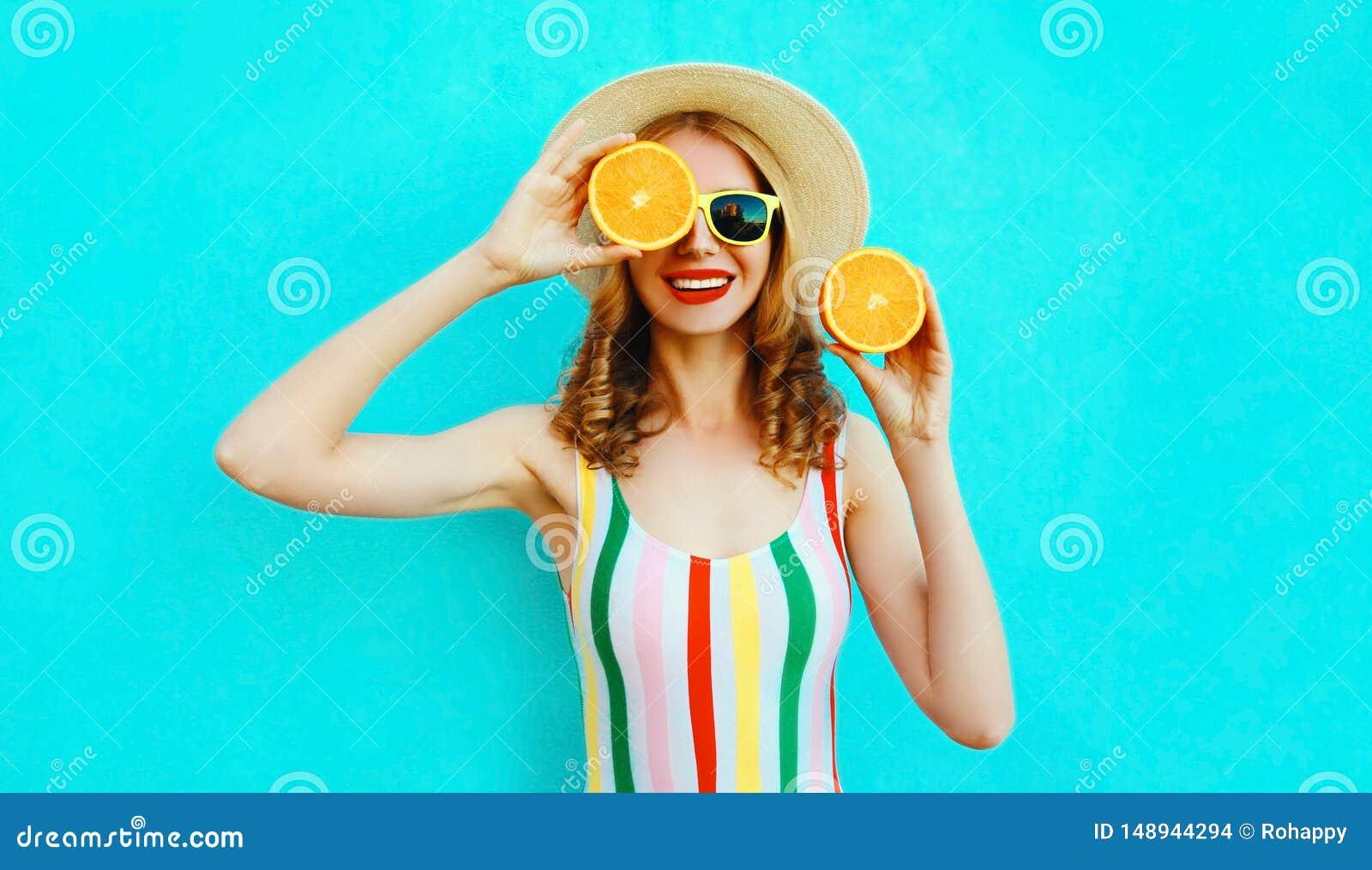 拿着在她的手上两个切片橙色果子的夏天画象微笑的妇女掩藏她的眼睛在五颜六色的蓝色的草帽