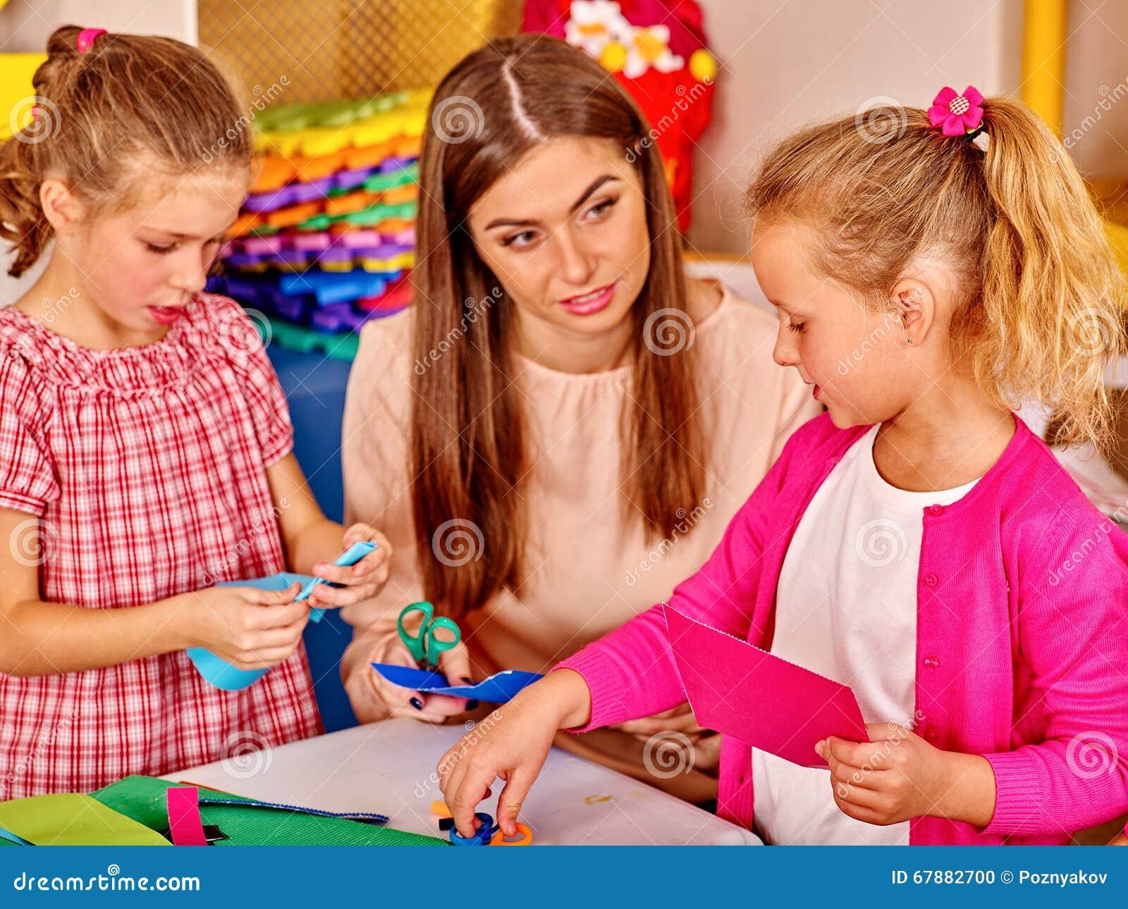 拿着在桌上的孩子色纸在幼儿园