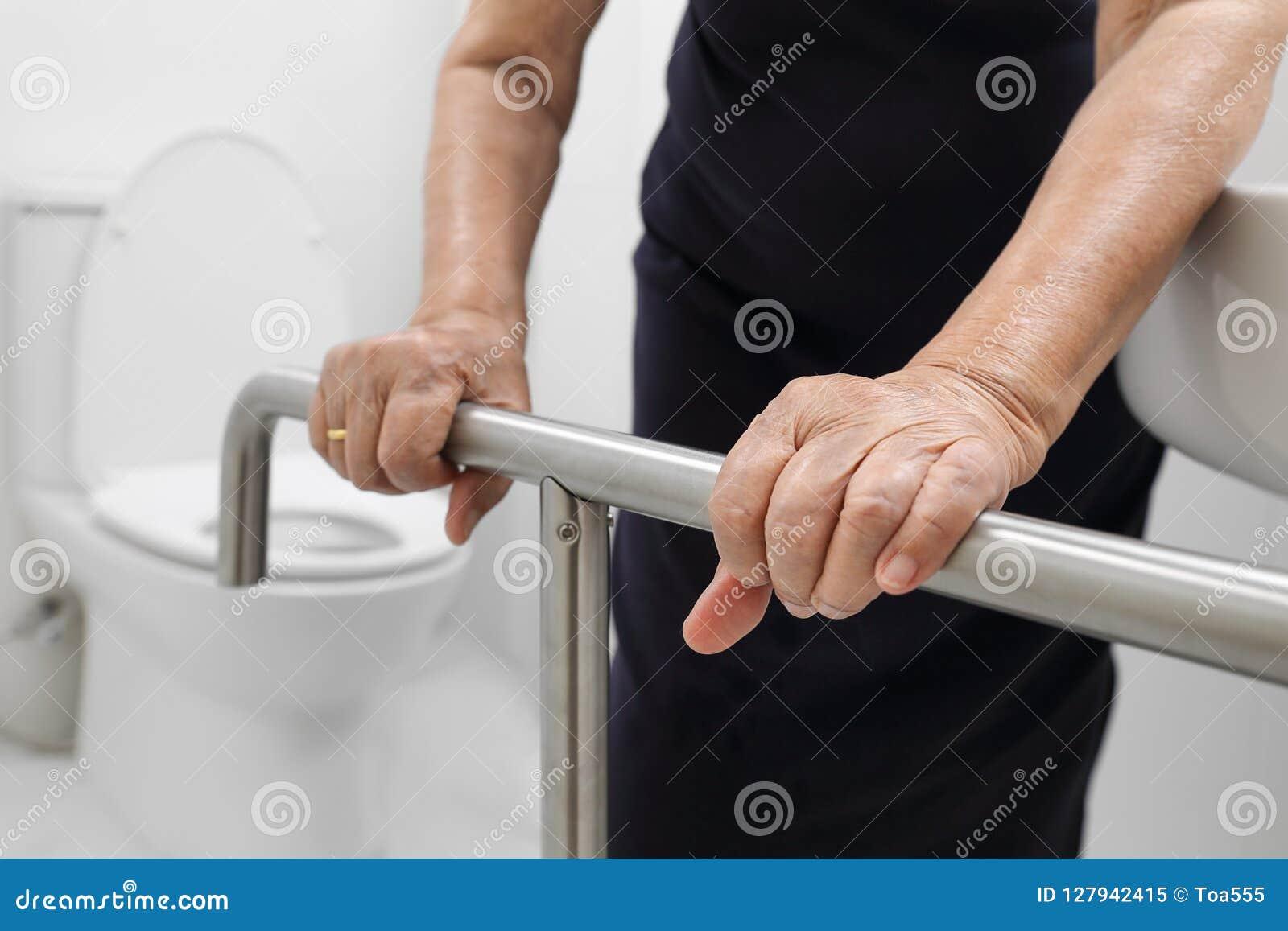 拿着在洗手间的年长妇女扶手栏杆