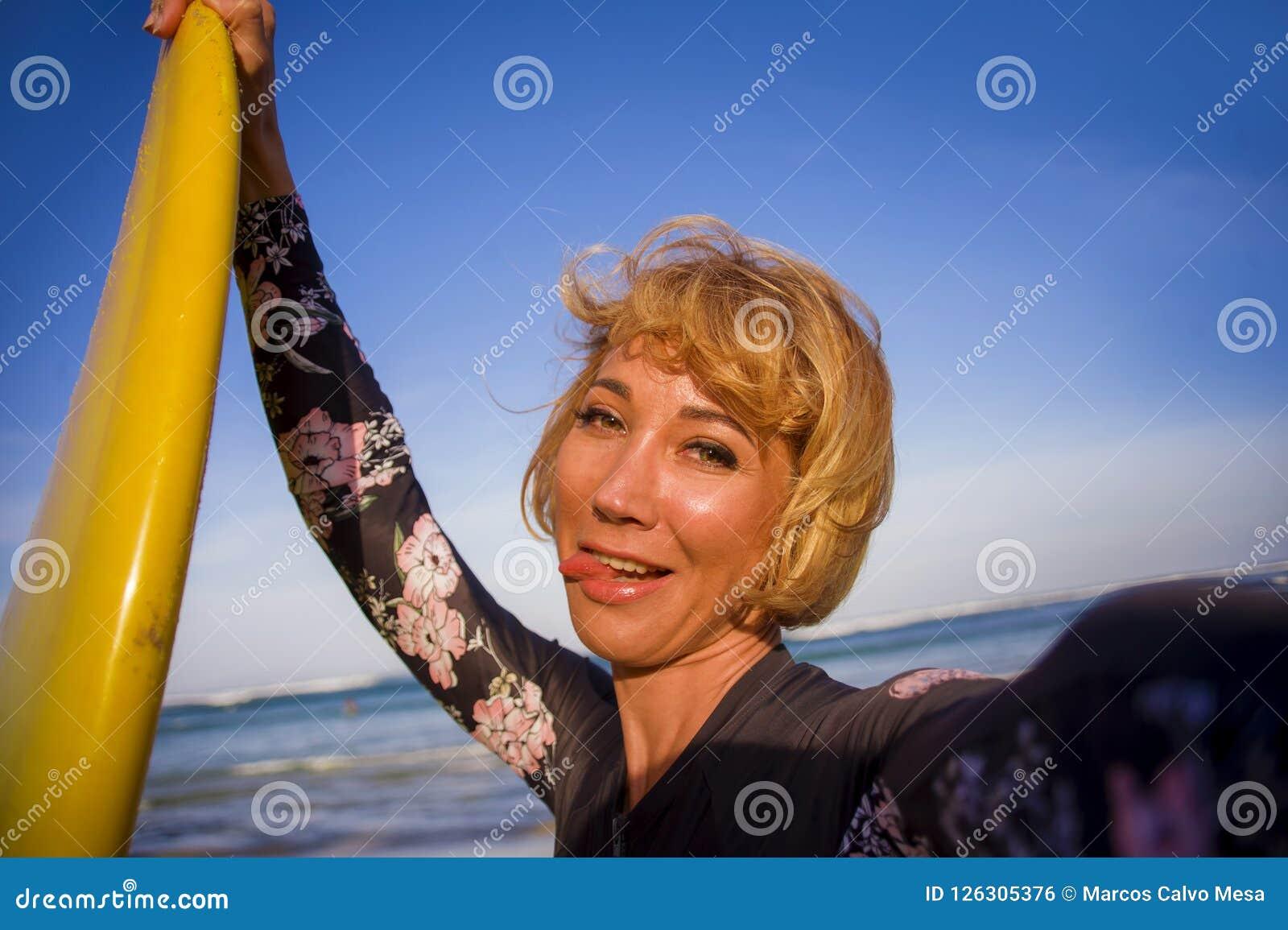 拿着在海滩的泳装的年轻可爱和愉快的白肤金发的冲浪者妇女水橇板采取自画象selfie图片smi