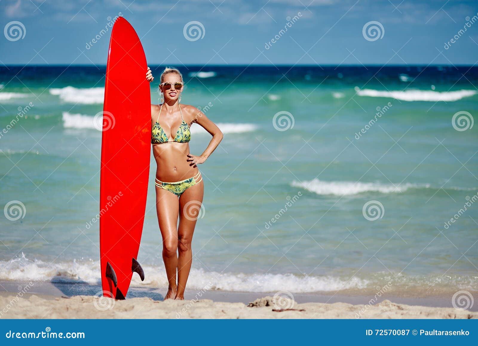 拿着在海边海滩的年轻俏丽的妇女冲浪板-充分len