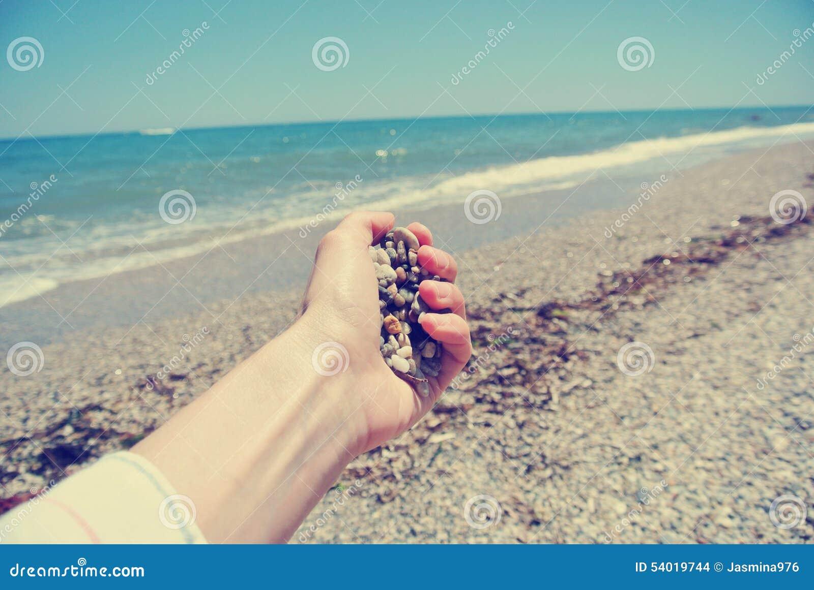 拿着在海滩的女性手小卵石,减速火箭/葡萄酒