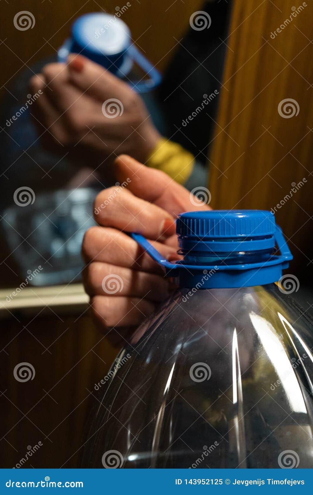 拿着在电梯的更老的资深妇女的手一个大蓝色塑料瓶