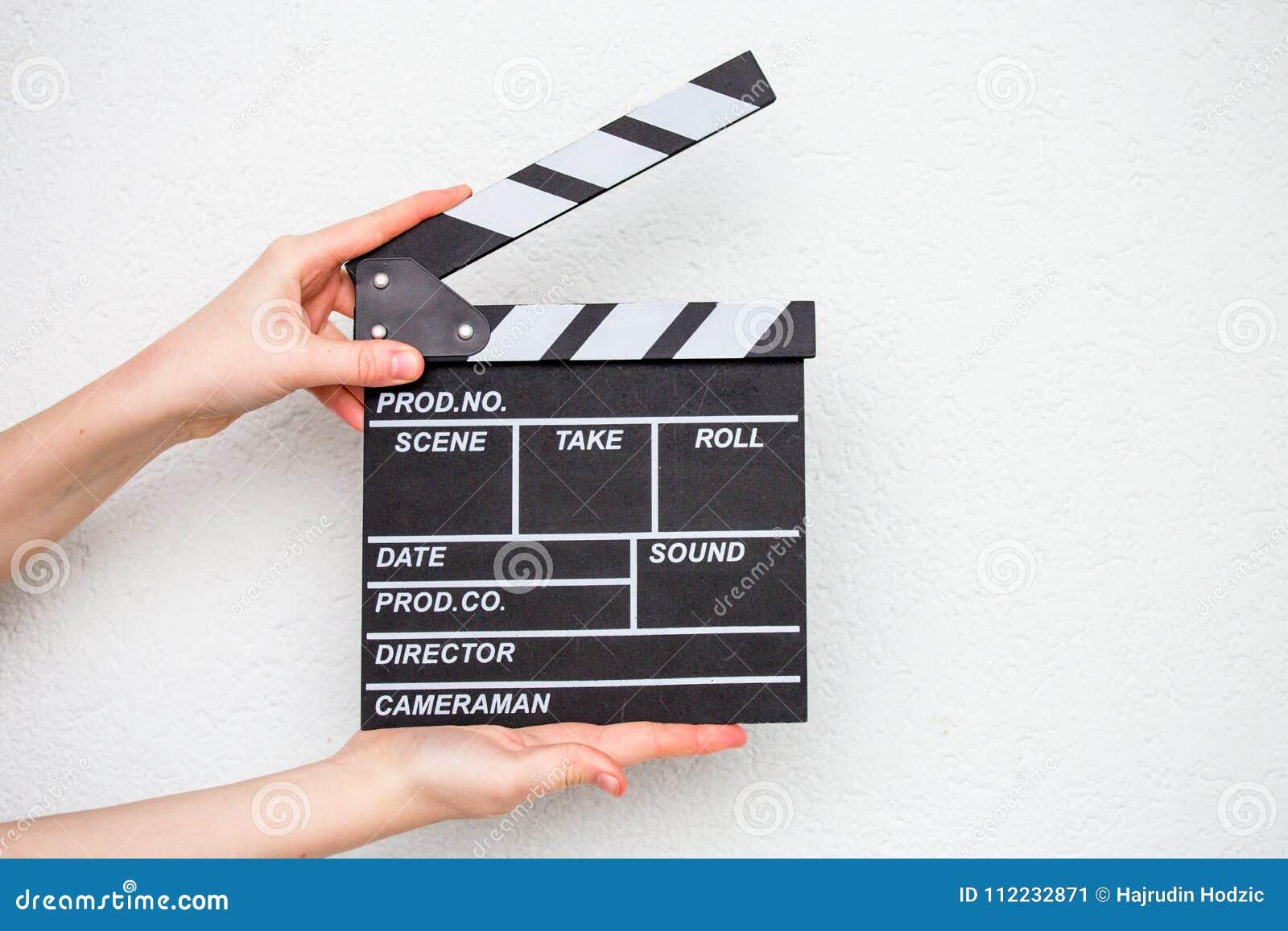 拿着在白色的女性手电影拍板
