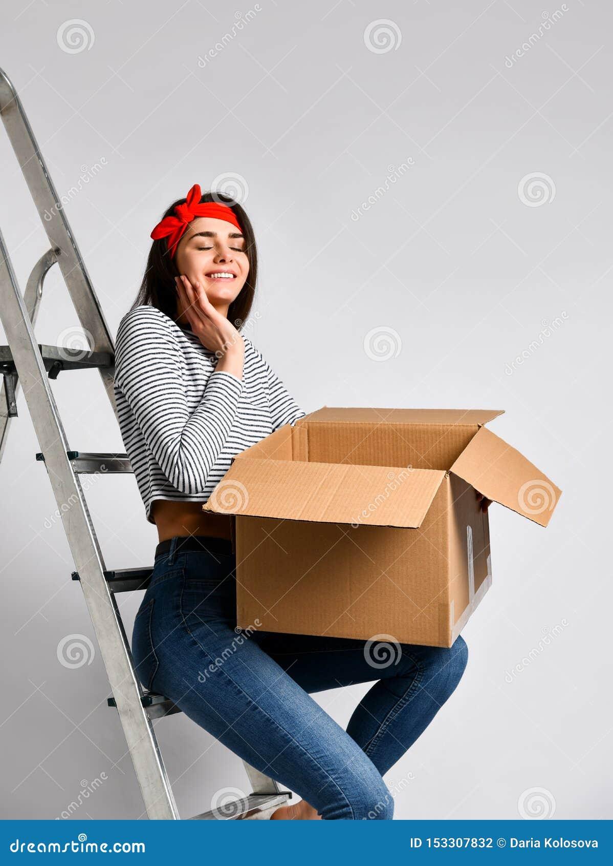 拿着在白色背景的微笑的年轻女人纸板箱