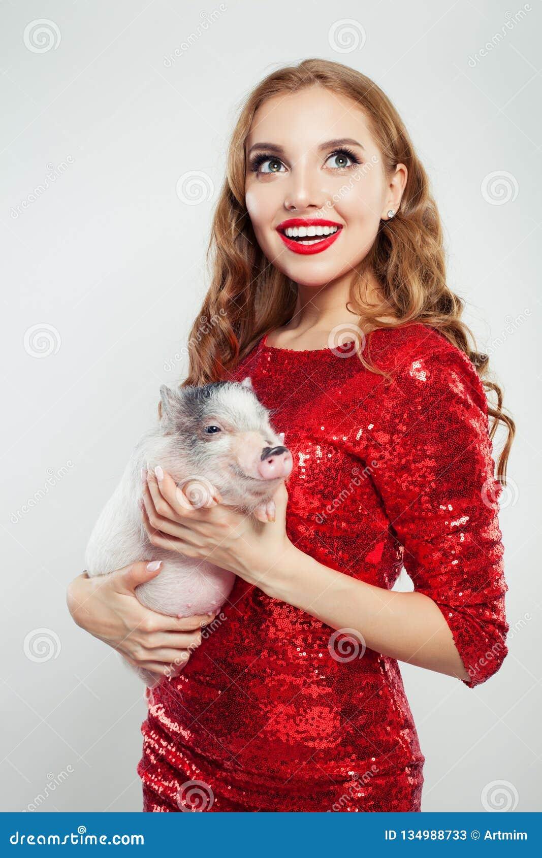 拿着在白色背景的红色时兴的礼服的逗人喜爱的激动的妇女微型猪