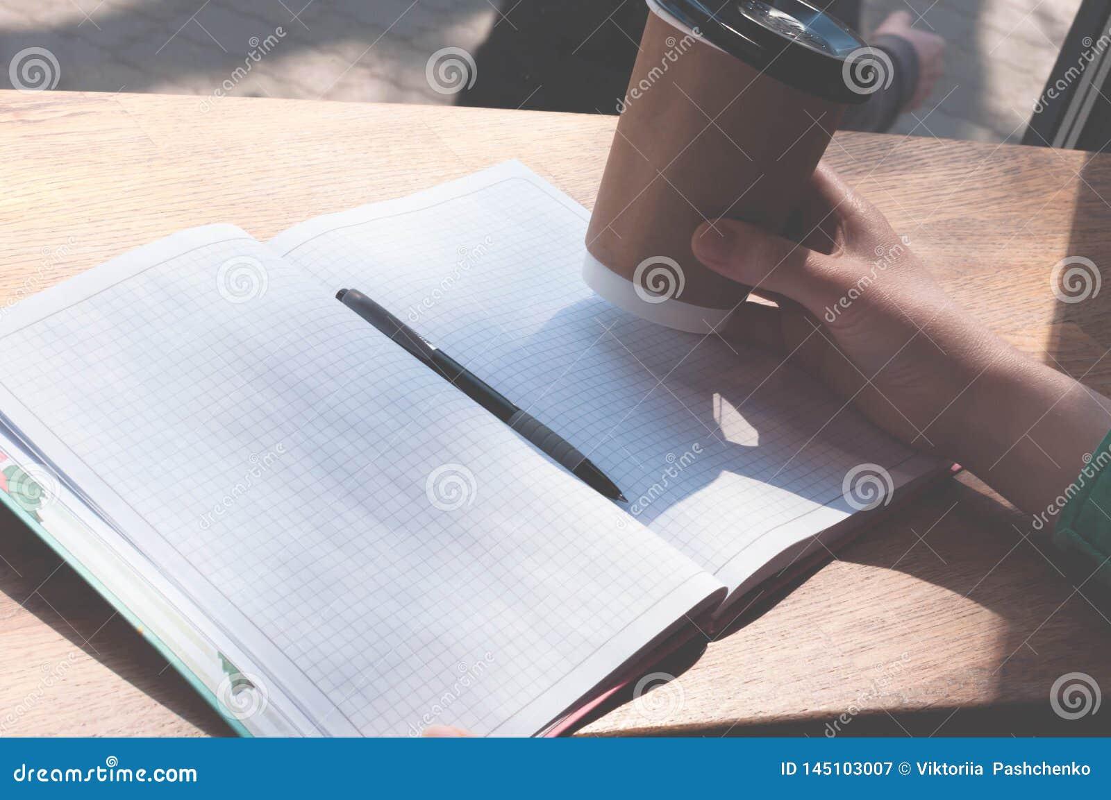 拿着在笔的有拷贝空间的Wooman纸杯和笔记本在木桌上在咖啡馆