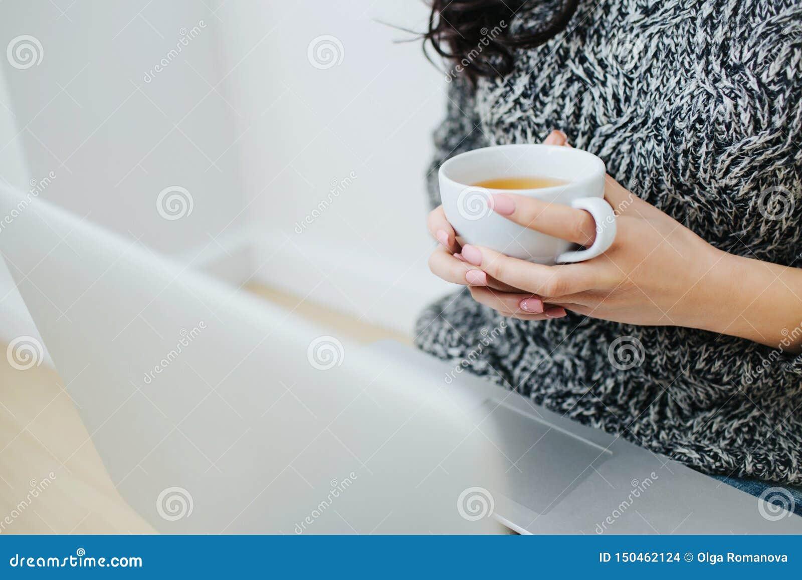 拿着在膝上型计算机前面的妇女的手杯子