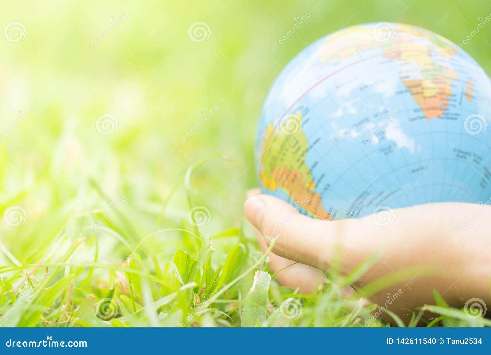 拿着在自然绿色背景的女性手浮动地球