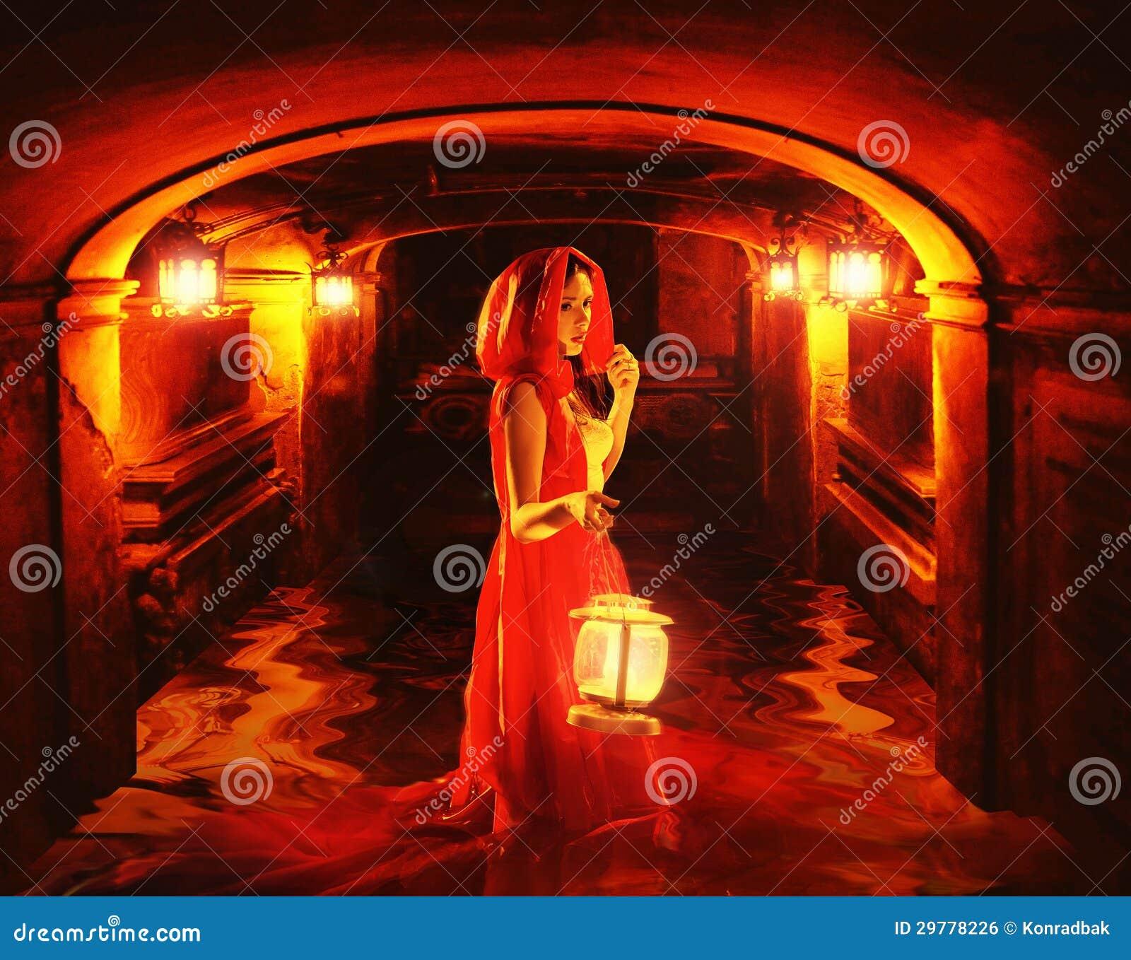 拿着在黑暗的土牢的红色的浪漫夫人一个灯笼