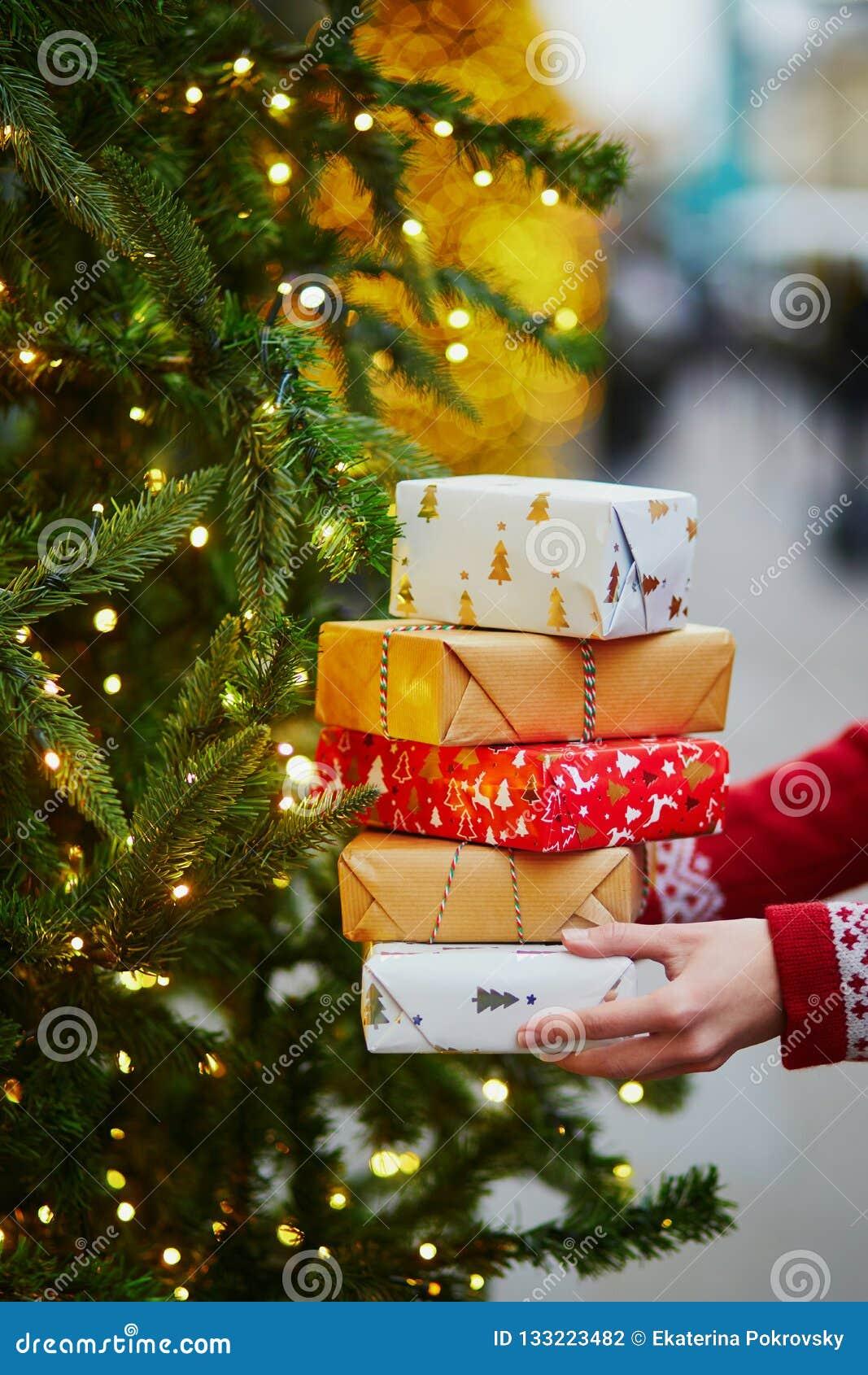 拿着堆圣诞礼物的妇女手