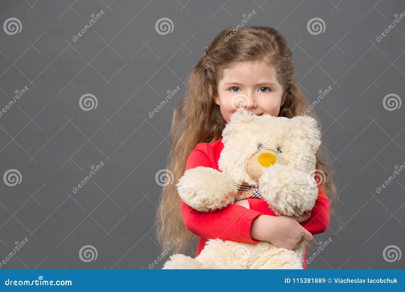 拿着她喜爱的玩具的快乐的逗人喜爱的女孩