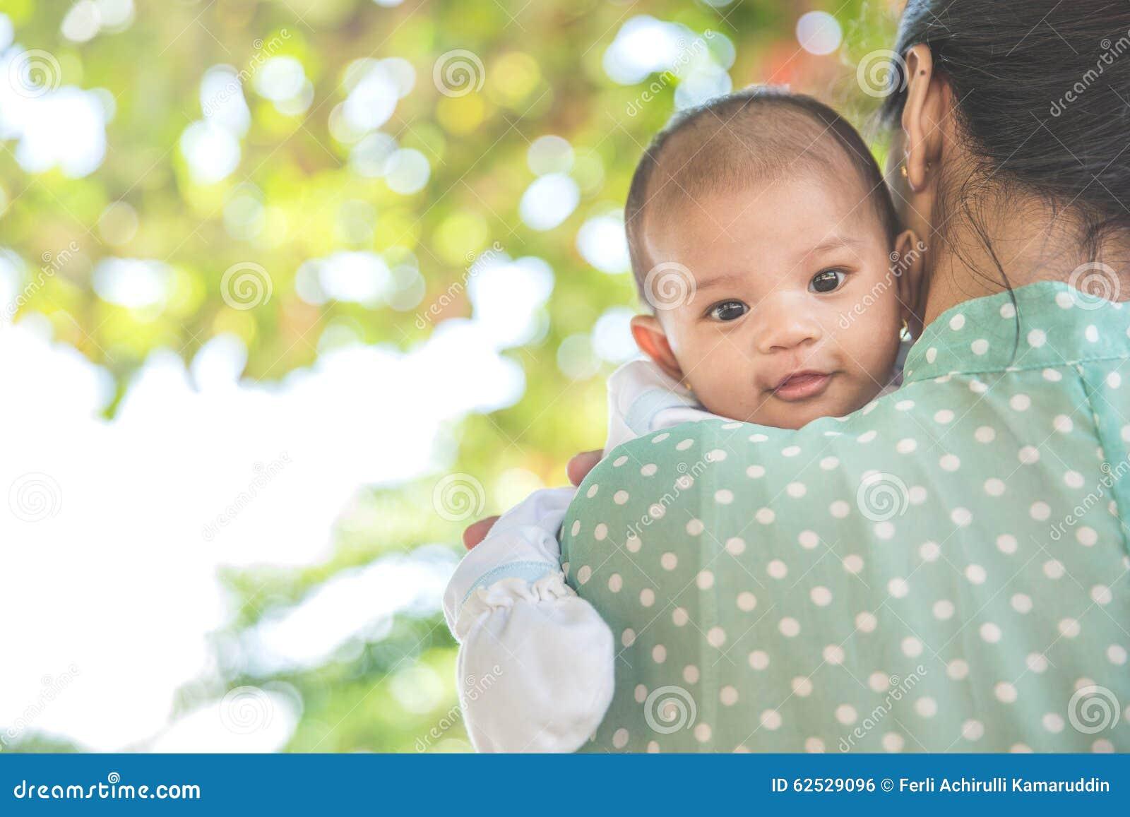 拿着她的小女儿,婴孩的妇女looing在照相机