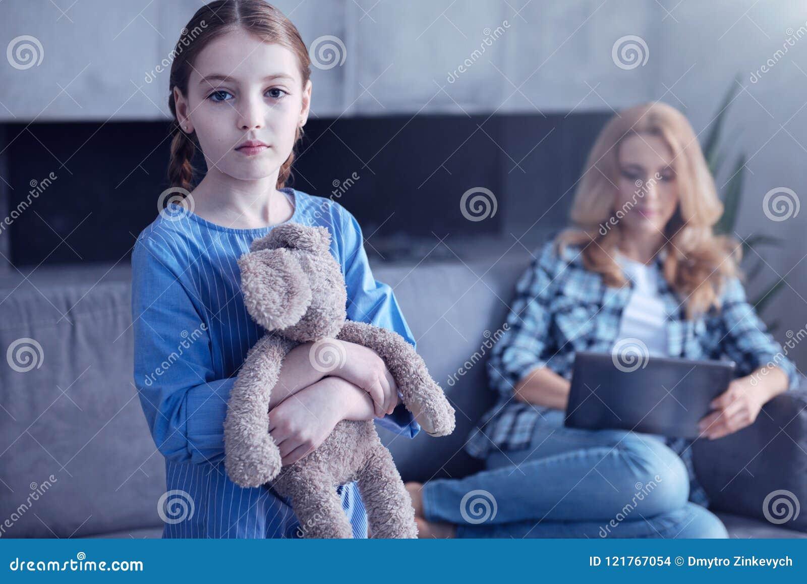 拿着她的玩具的哀伤的不快乐的女孩