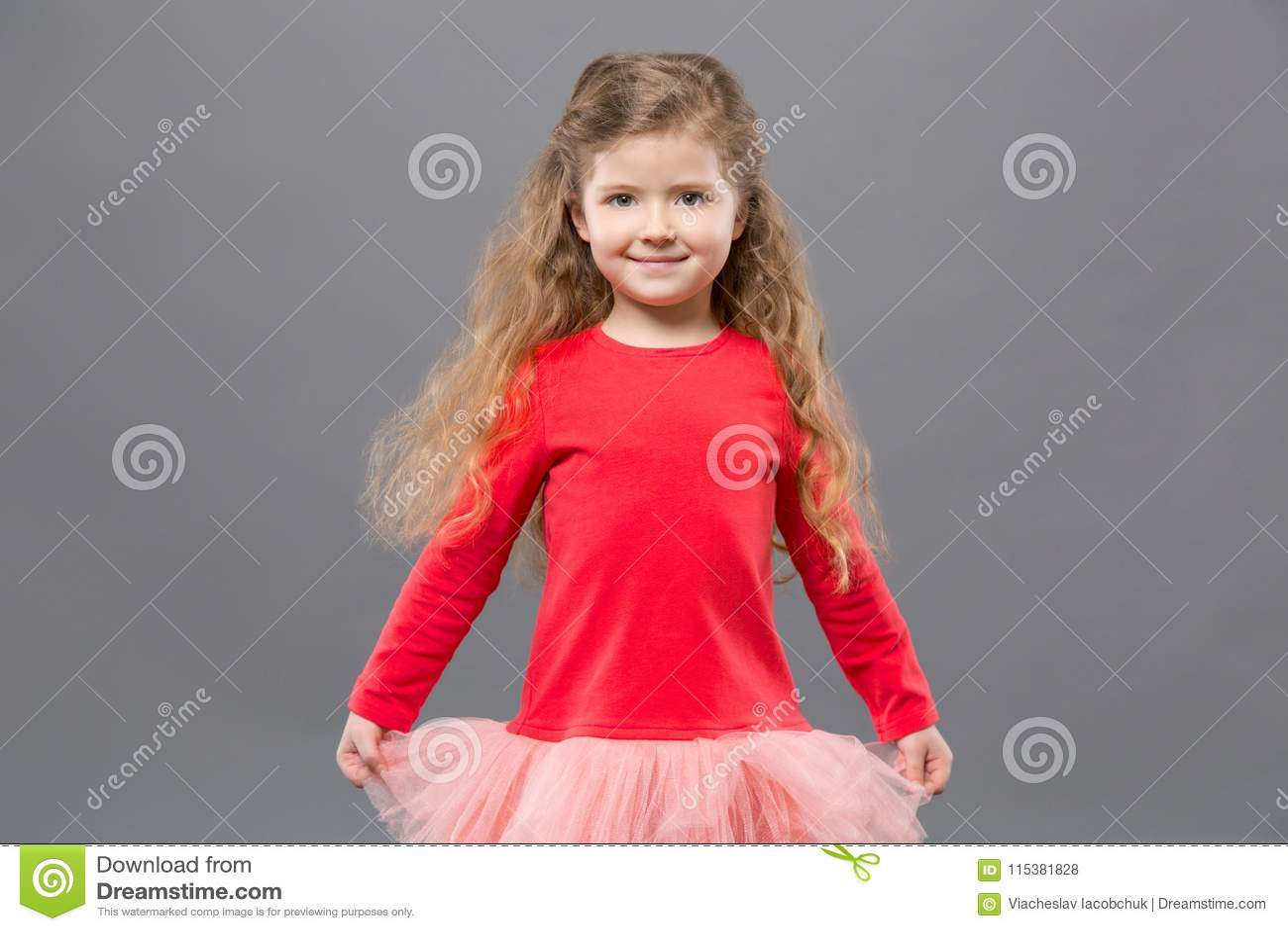 拿着她的礼服的逗人喜爱的好女孩