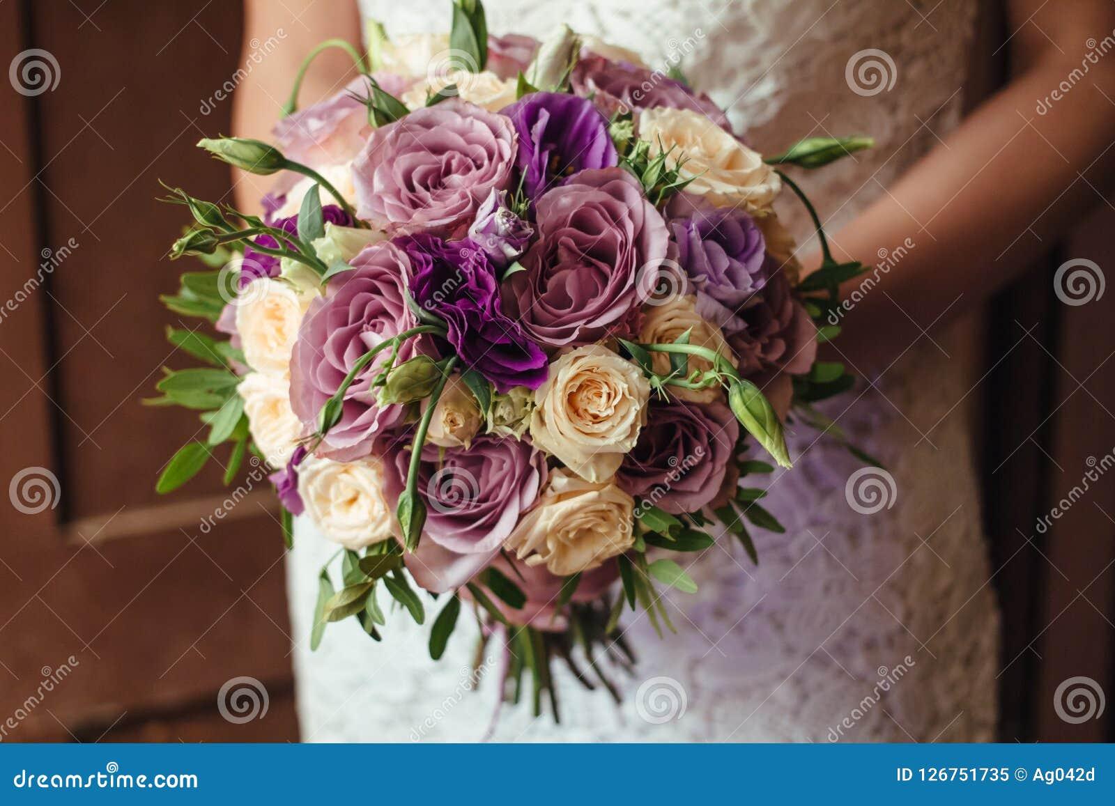 拿着婚礼花束,新娘花束的白色礼服的年轻美丽的新娘从玫瑰色奶油色浪花,玫瑰丛,玫瑰紫色Memor的