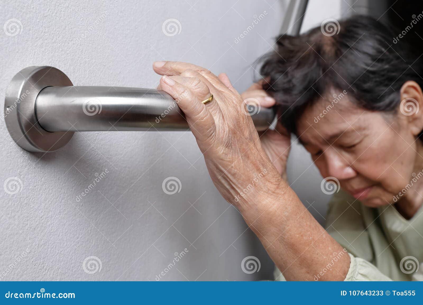 拿着安全步行的年长妇女扶手栏杆