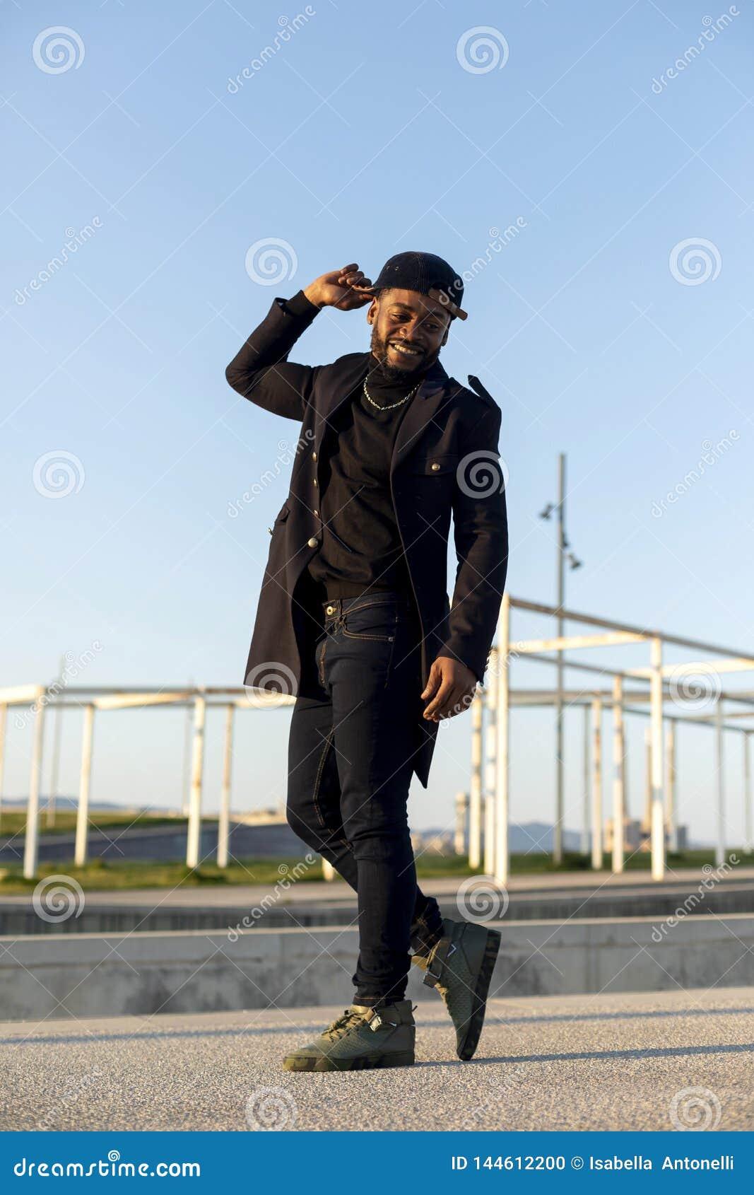 拿着帽子的一个黑人有胡子的人的正面图,当跳舞和享用反对天空蔚蓝在一好日子时