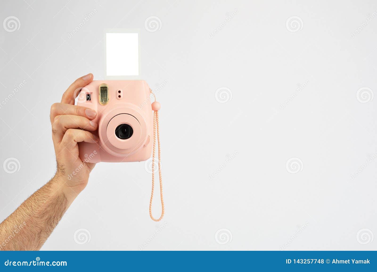 拿着快速照相机的男性手