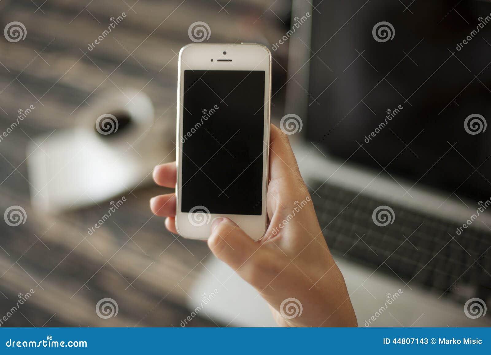 拿着手机和膝上型计算机和咖啡杯在ba的妇女手