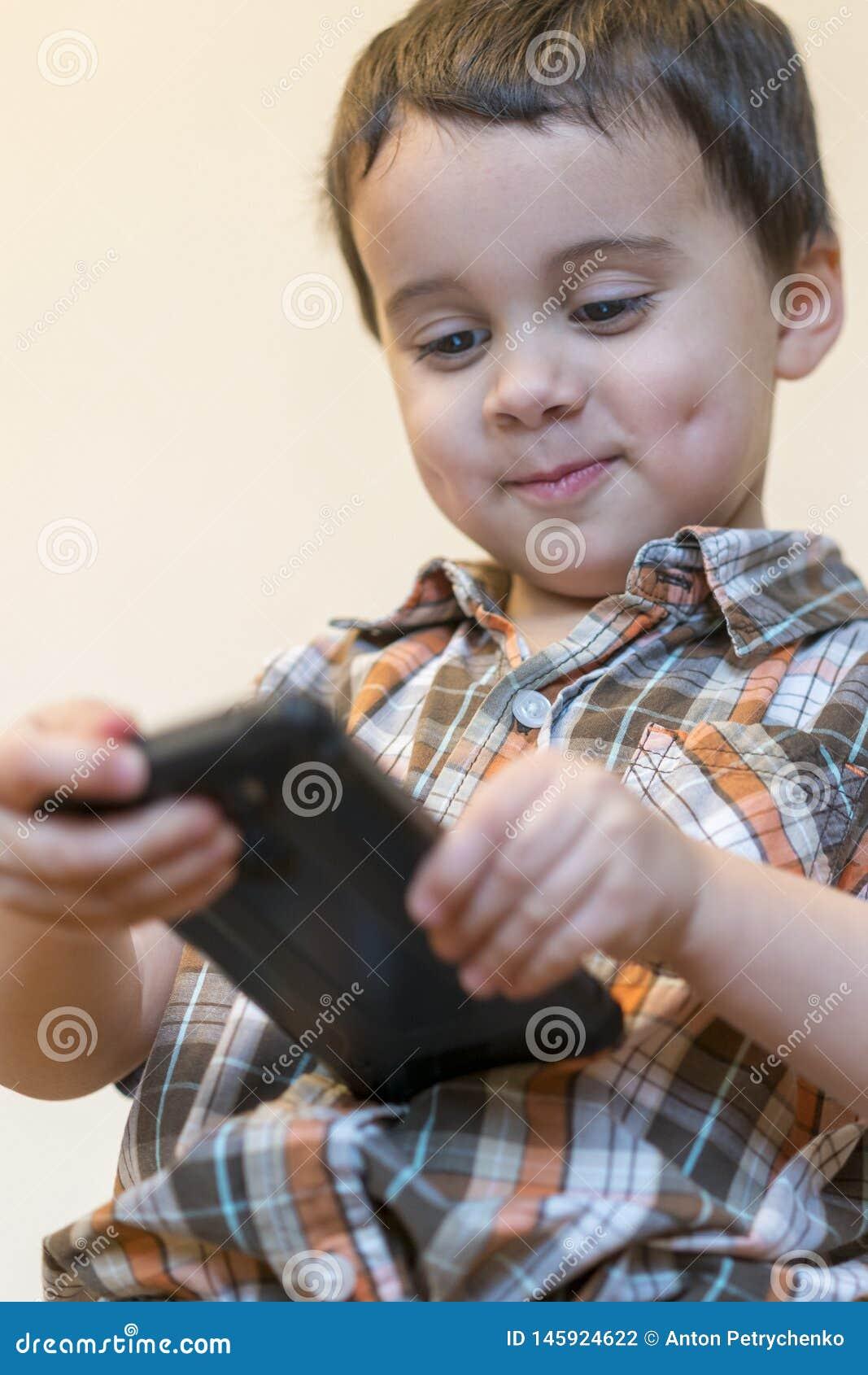 拿着手机的一个微笑的小男孩的画象被隔绝在轻的背景 打在智能手机的逗人喜爱的孩子比赛