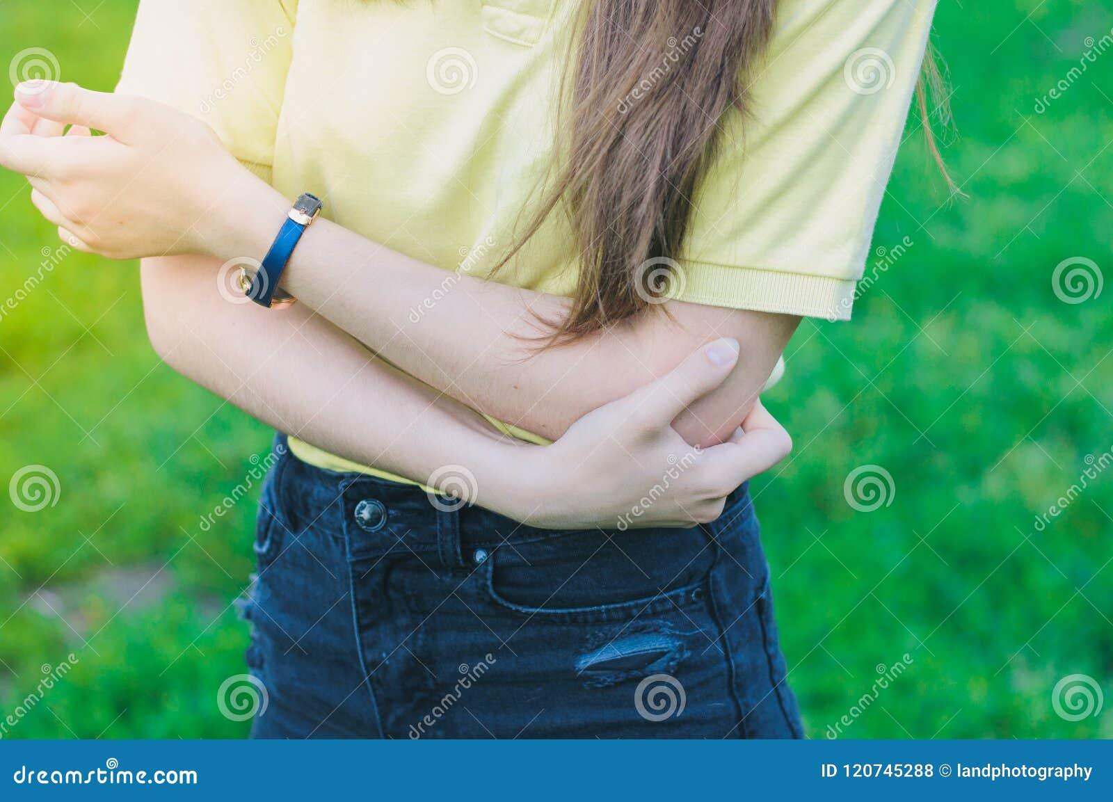 拿着手肘的妇女 胳膊疼痛