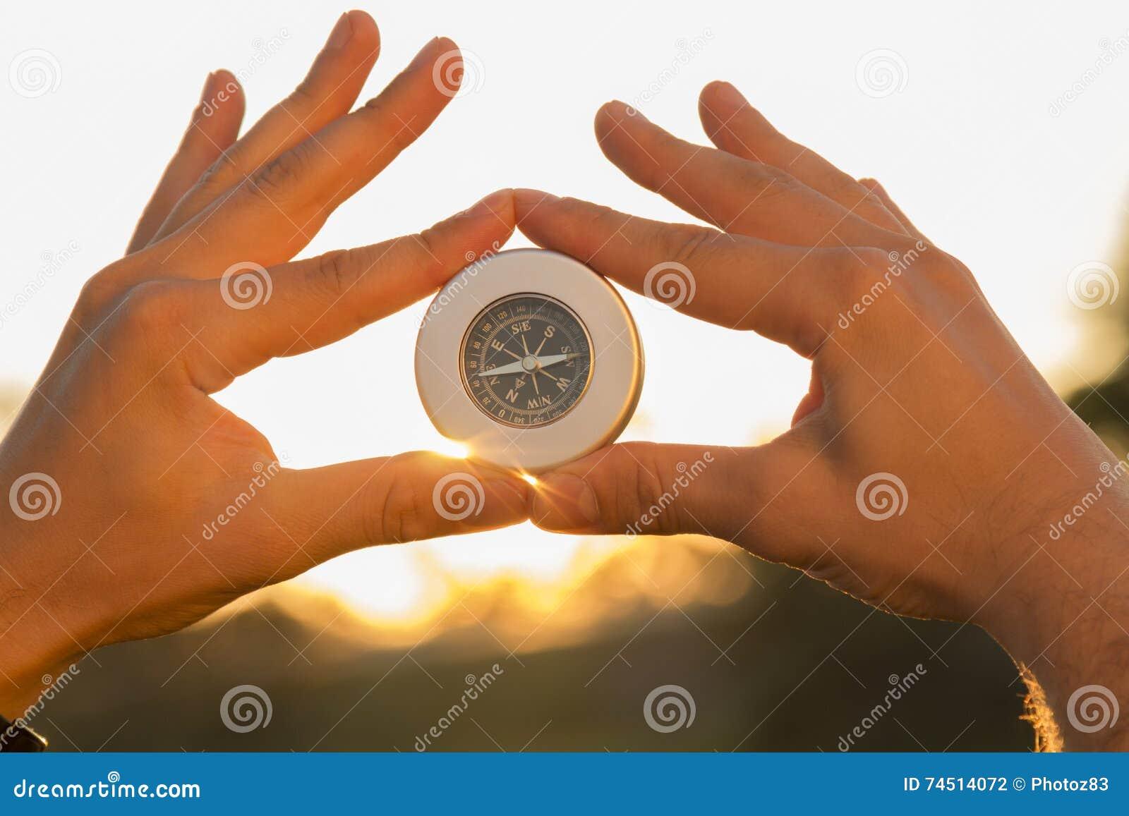 拿着指南针的手在日落