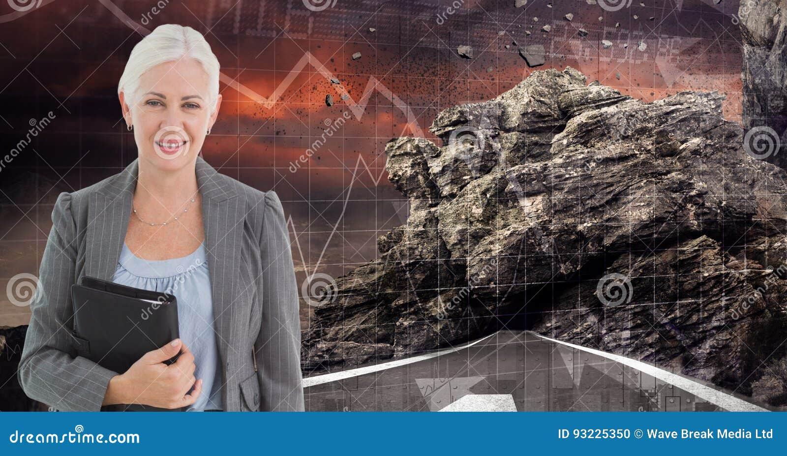 拿着日志的女实业家的数字图象,当站立在路反对岩石和图表时