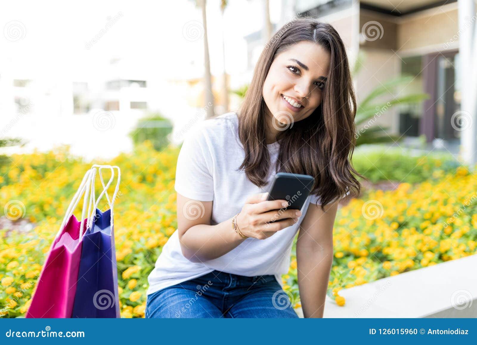 拿着智能手机的妇女,当坐由在购物之外时的袋子
