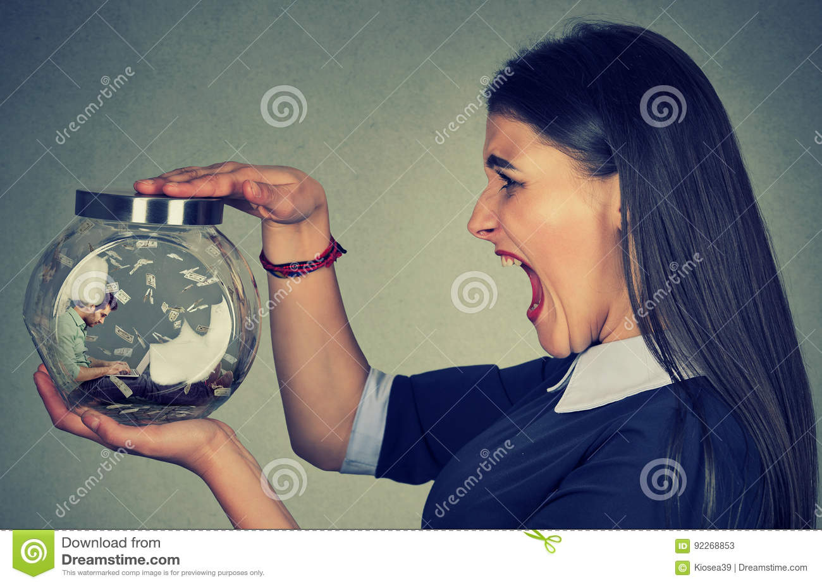拿着有一个人的恼怒的妇女一个玻璃瓶子研究被困住的膝上型计算机里面