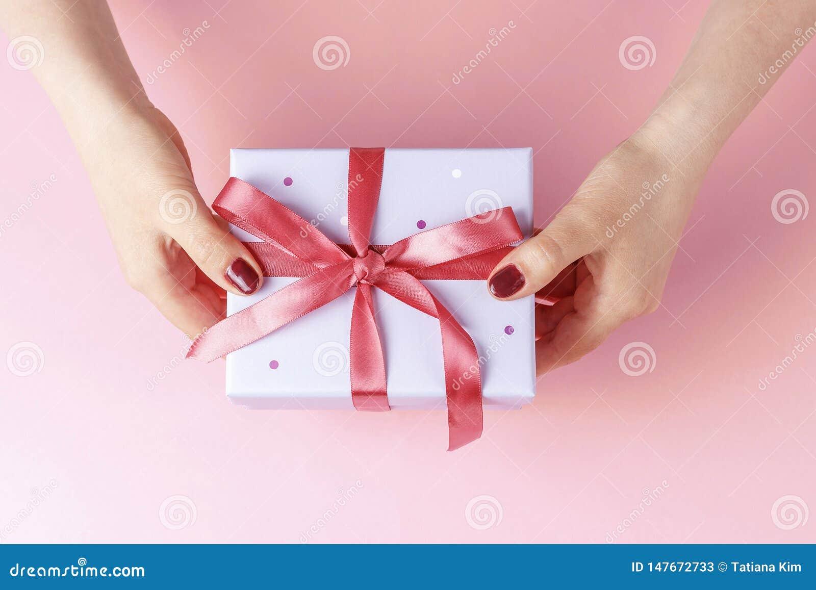 拿着有丝带的女性手礼物盒在桃红色背景,顶视图