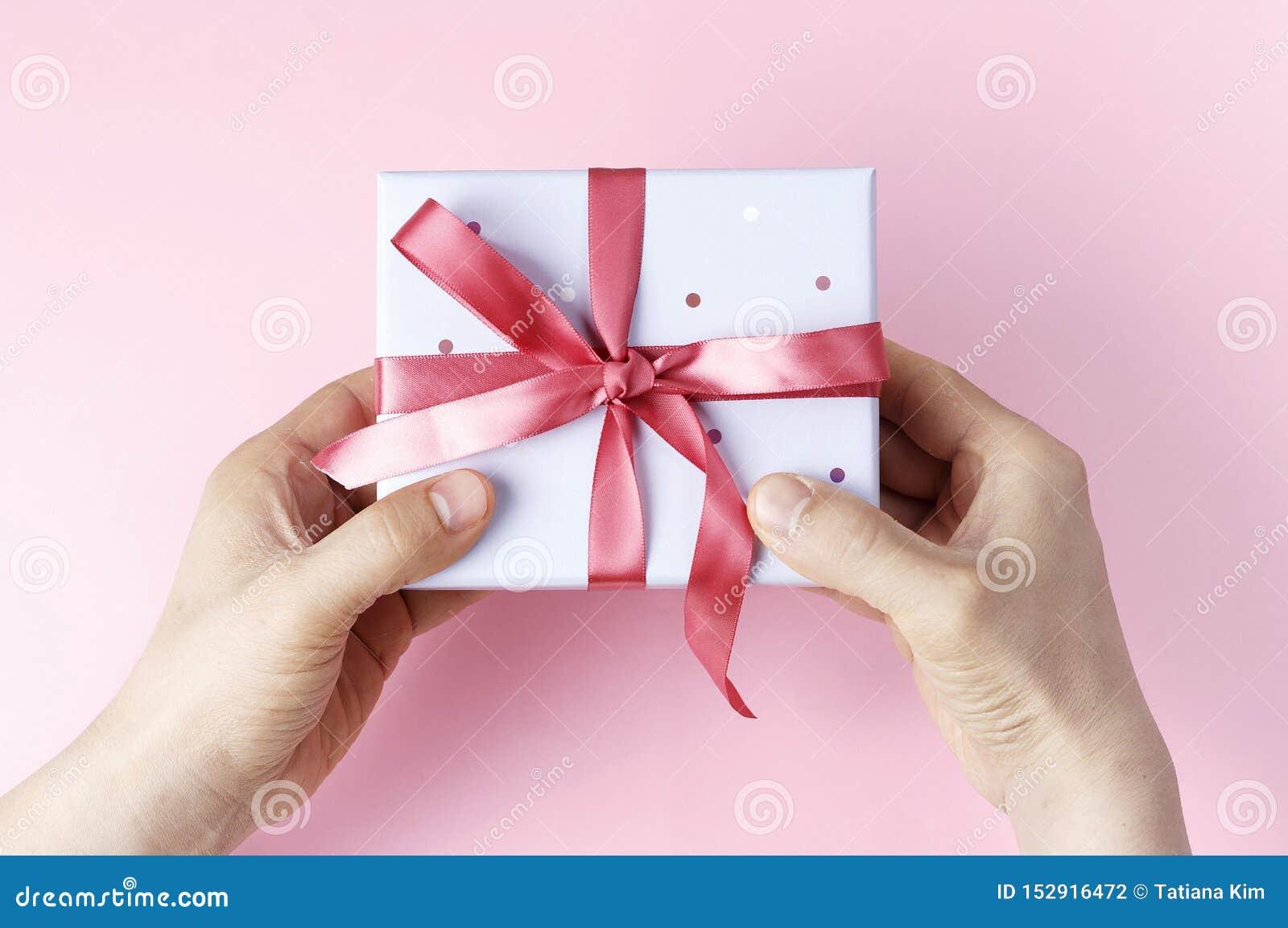 拿着有丝带的男性手礼物盒在桃红色背景,顶视图