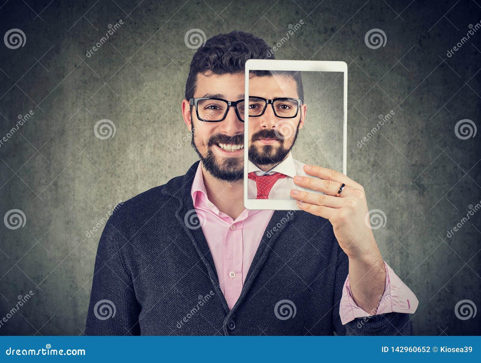 拿着有严肃的自画象的快乐的人一种片剂在屏幕上