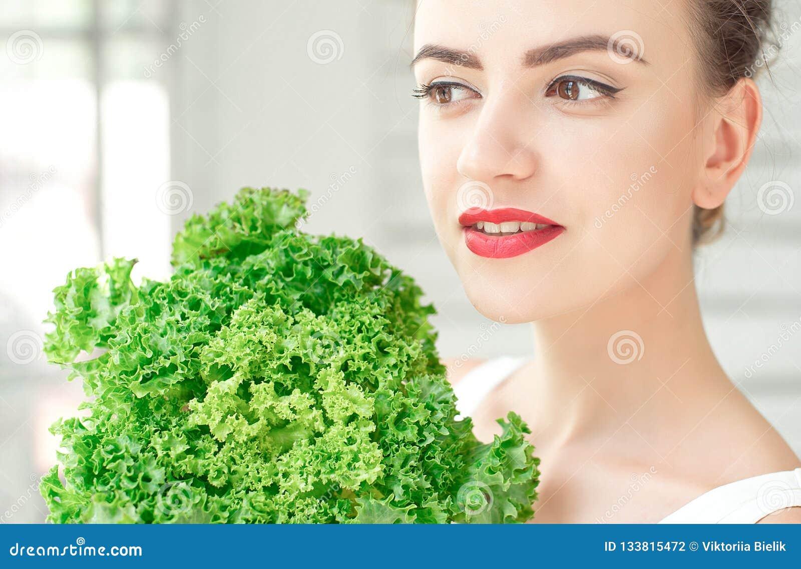拿着有机绿色散叶莴苣的年轻逗人喜爱的微笑的女孩在面孔附近 Healtlife概念