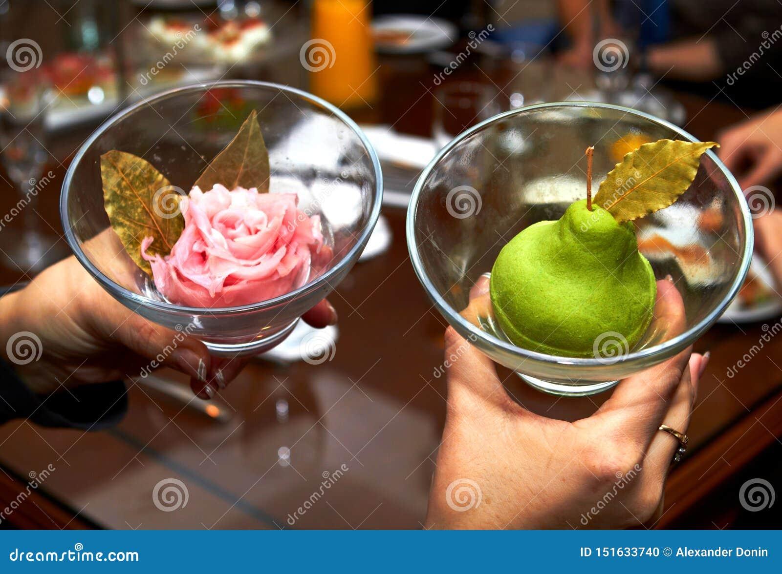 拿着有梨状的冰淇淋的女性手两个花瓶