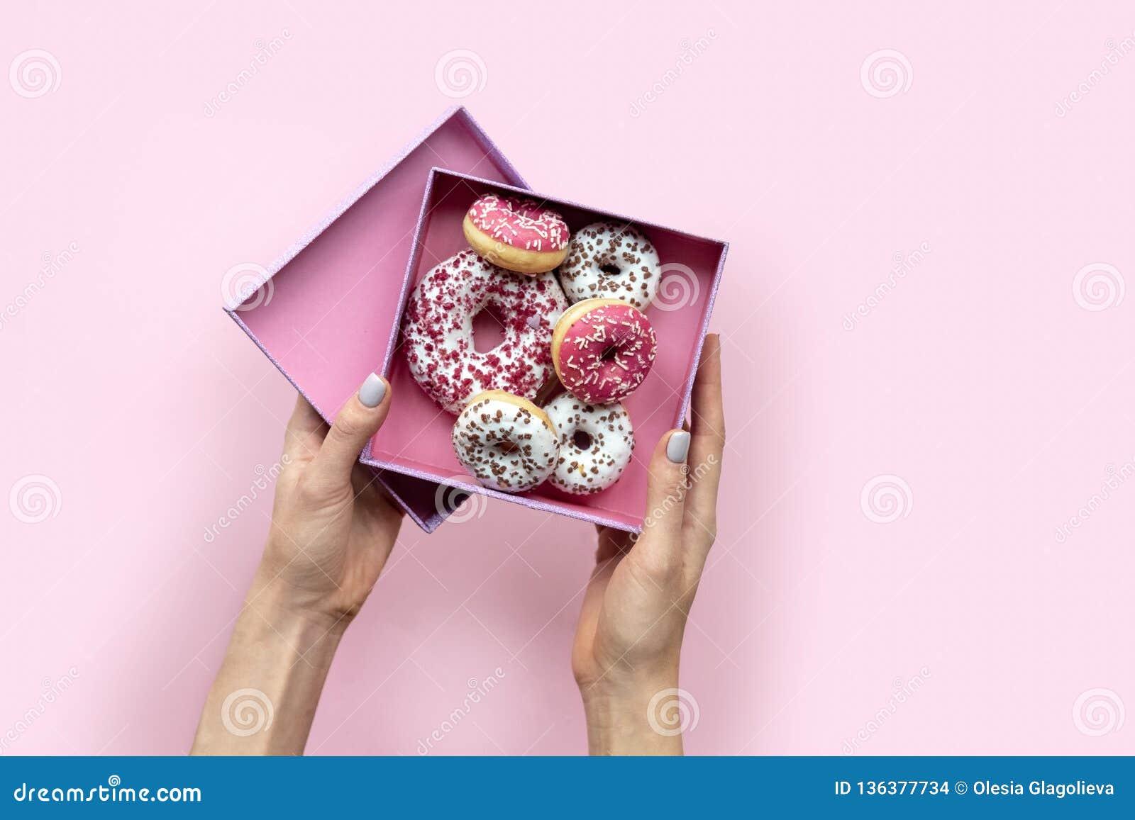 拿着有油炸圈饼的妇女手开放箱子在桃红色背景 平的位置样式